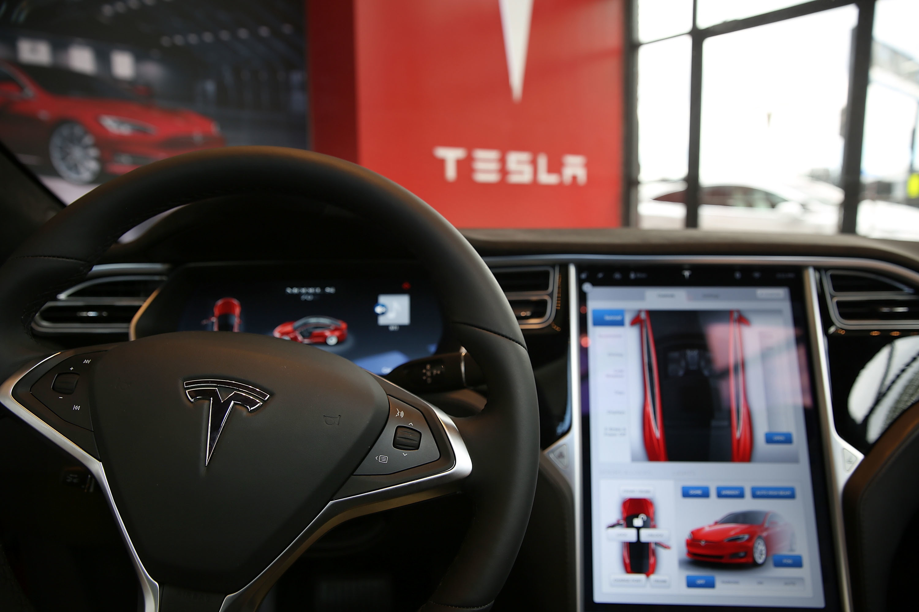 """Tesla's touch screen (on right) will now show you how many cars are charging up at a nearby """"Supercharger"""" charging station."""