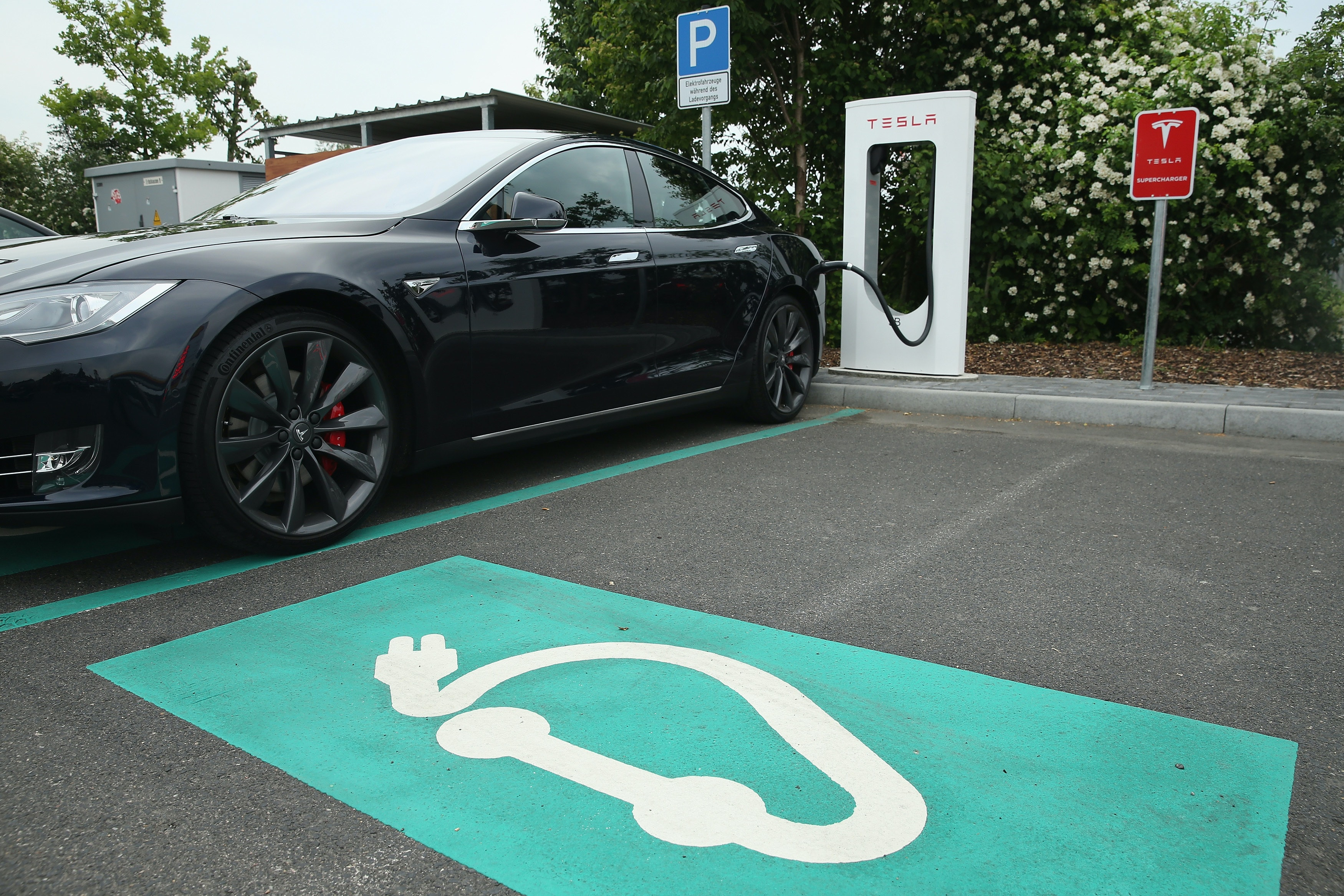 RIEDEN, GERMANY - JUNE 11:  A Tesla electric-powered sedan stands at a Tesla charging staiton at a highway reststop along the A7 highway on June 11, 2015 near Rieden, Germany. Tesla has introduced a limited network of charging stations along the German highway grid in an effort to raise the viability for consumers to use the cars for longer journeys.  (Photo by Sean Gallup/Getty Images)