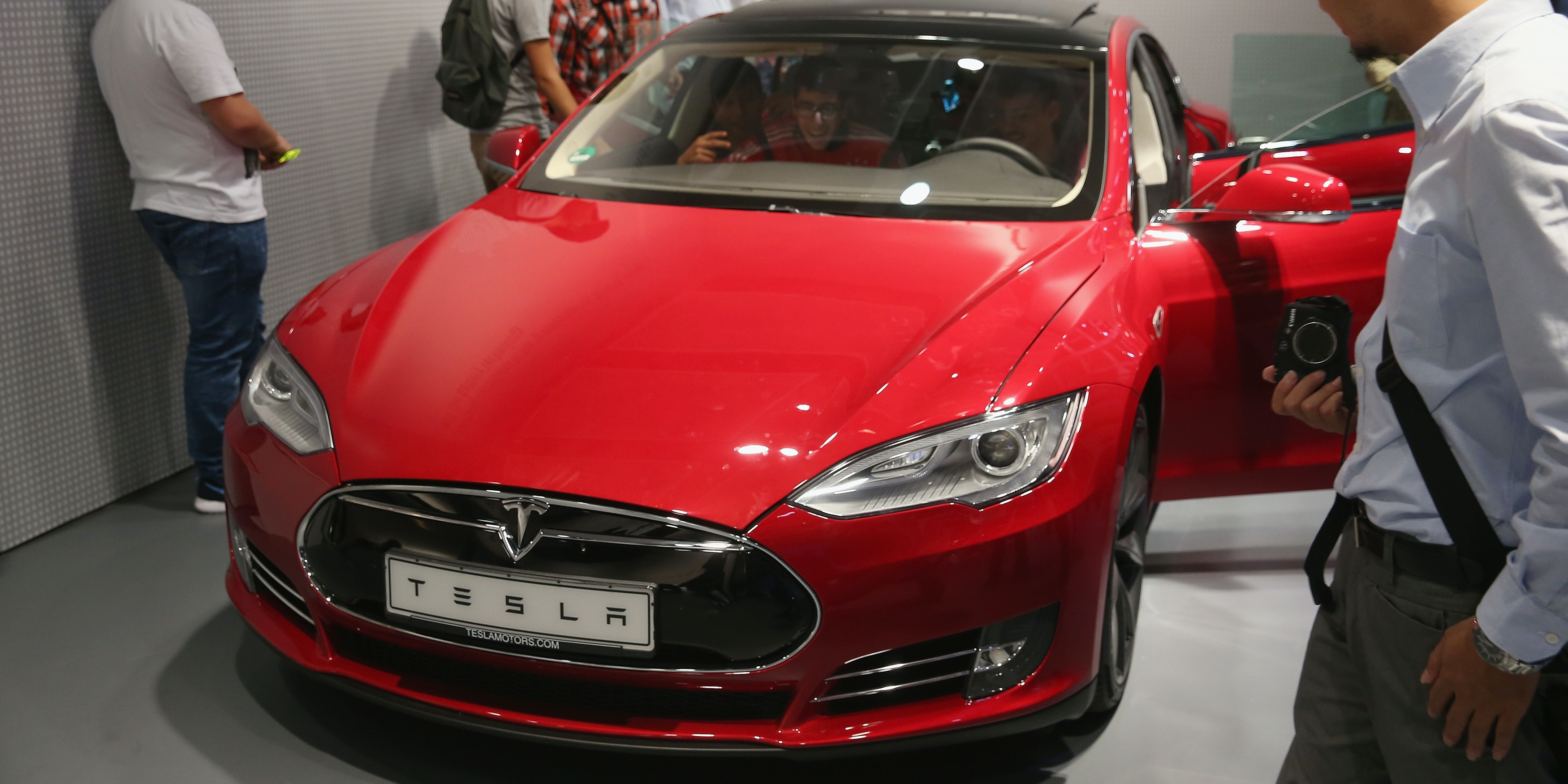 BERLIN, GERMANY - SEPTEMBER 05:  Visitors look at a Tesla Model S electric car at the Panasonic stand at the 2014 IFA home electronics and appliances trade fair on September 5, 2014 in Berlin, Germany. IFA is the world's biggest fair of its kind and is open to the public through September 10.  (Photo by Sean Gallup/Getty Images)