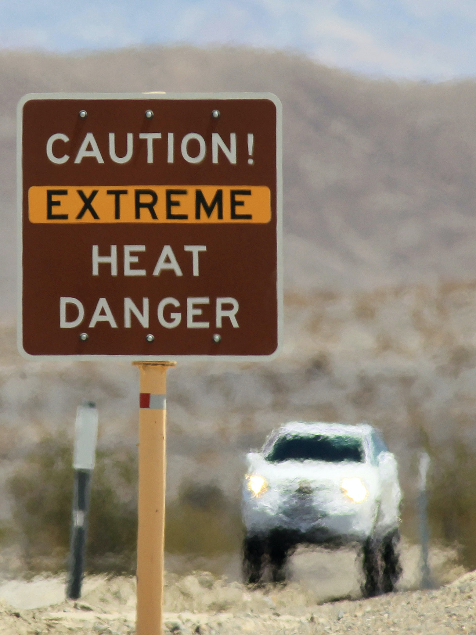 Heat waves rise near a heat danger warning sign on the eve of the AdventurCORPS Badwater 135 ultra-marathon race on July 14, 2013 in Death Valley National Park, California.