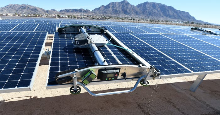 A panel washing robot cleans a row of solar panels during a dedication ceremony to commemorate the completion of the 102-acre, 15-megawatt Solar Array II Generating Station at Nellis Air Force Base on February 16, 2016 in Las Vegas, Nevada.