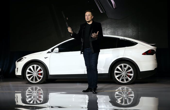 Elon Musk speaking in front of the Tesla Model X. Newer versions come with sensors intended for autonomous driving.