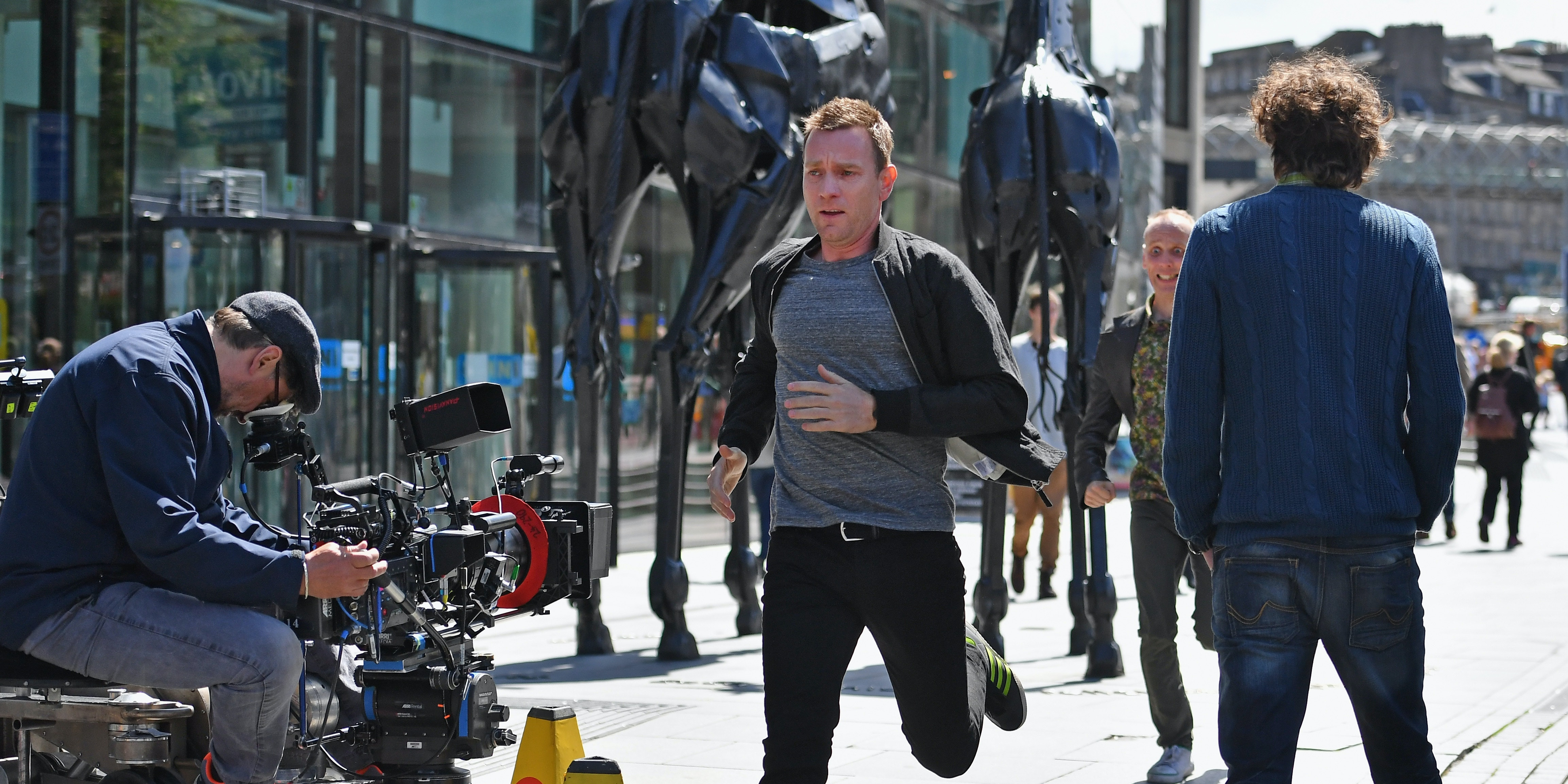 EDINBURGH, SCOTLAND - JULY 13:  Actors Ewan McGregor and Ewan Bremner runs on the set of the Trainspotting film sequel on Princess Street on July 13, 2016 in Edinburgh, Scotland. The long awaited Trainspotting 2 is being filmed in Edinburgh and Glasgow, 20 years after the original was released and it will also see the cast from the first film returning including Ewan McGregor, Jonny Lee Miller and Robert Carlyle.  (Photo by Jeff J Mitchell/Getty Images)
