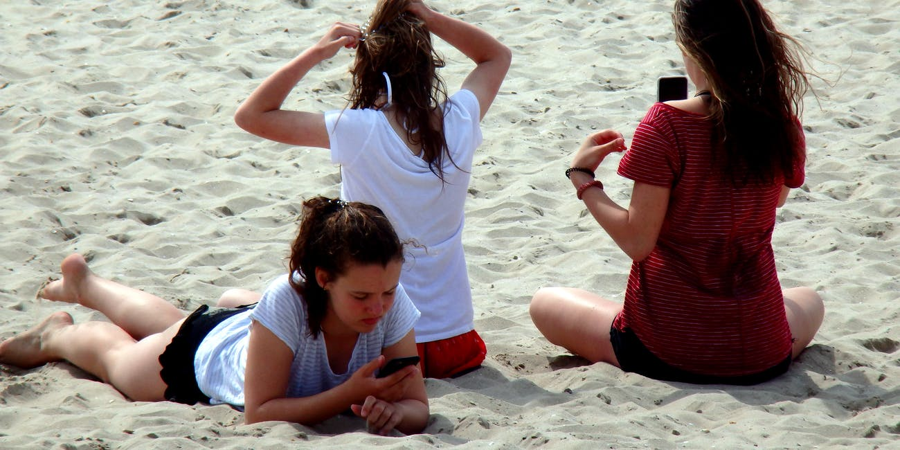 Girls on beach addicted to their smartphones