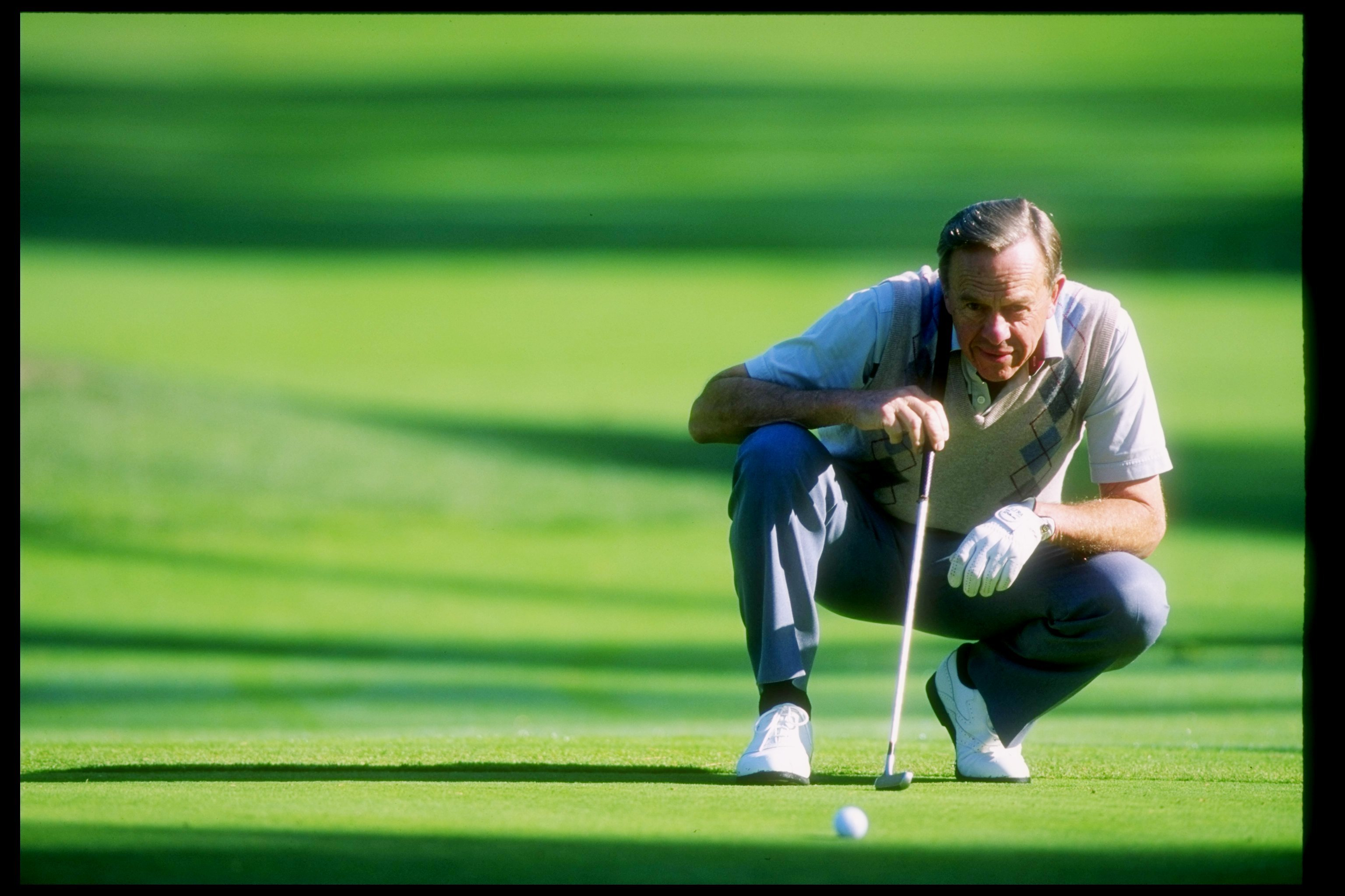 Former NASA astronaut Alan Shephard lines up a shot during a golfing event.