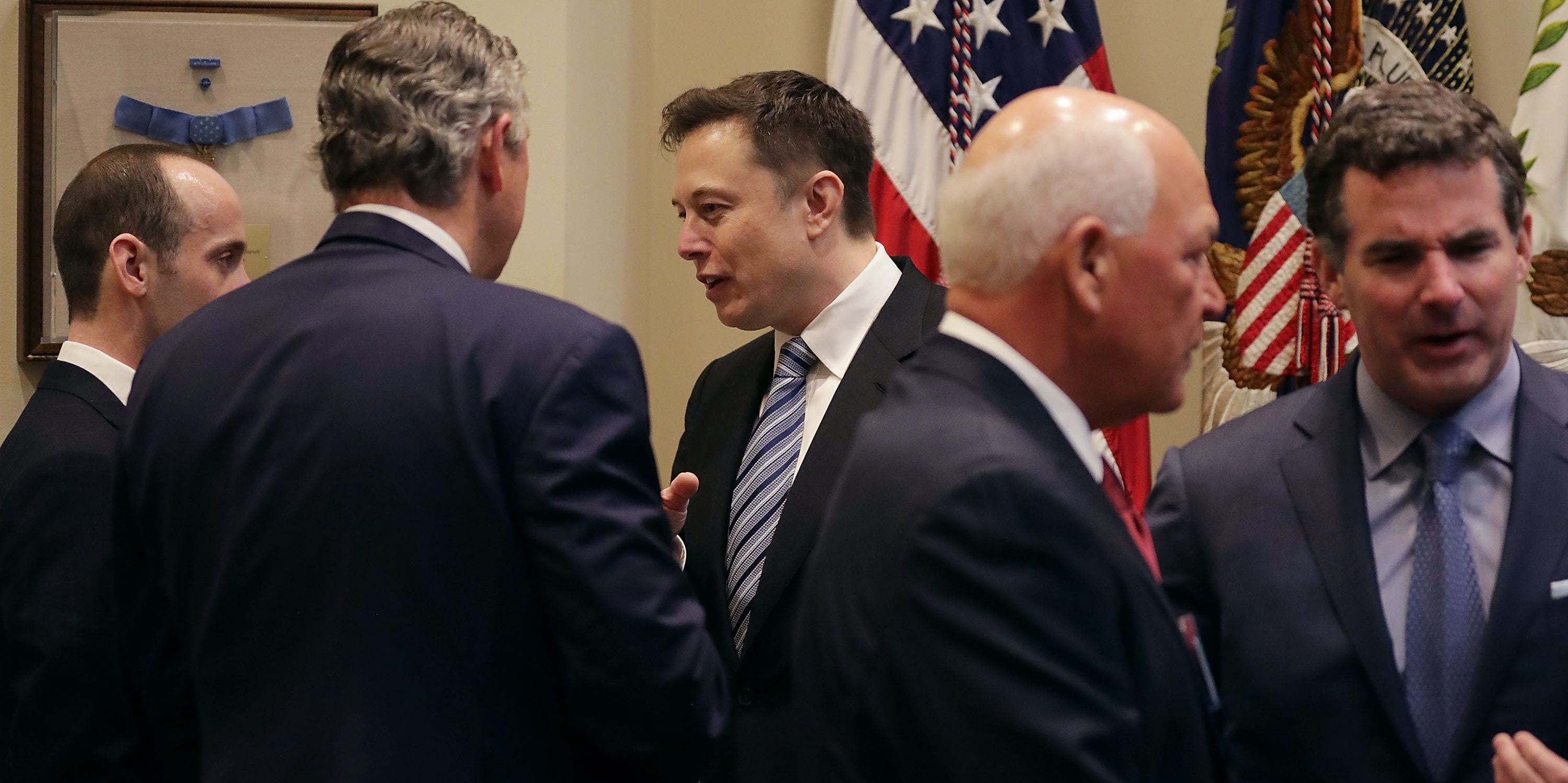 WASHINGTON, DC - JANUARY 23:  White House Senior Advisor Stephen Miller (L) and Klaus Kleinfeld of Arconic visit with Elon Musk (C) of SpaceX before a meeting with U.S. President Donald Trump in the Roosevelt Room at the White House January 23, 2017 in Washington, DC. Business leaders who also attend the meeting included Elon Musk of SpaceX, Mark Sutton of International Paper, Michael Dell of Dell Technologies, Marillyn Hewson of Lockheed Martin, Andrew Liveris of Dow Chemical and others.  (Photo by Chip Somodevilla/Getty Images)
