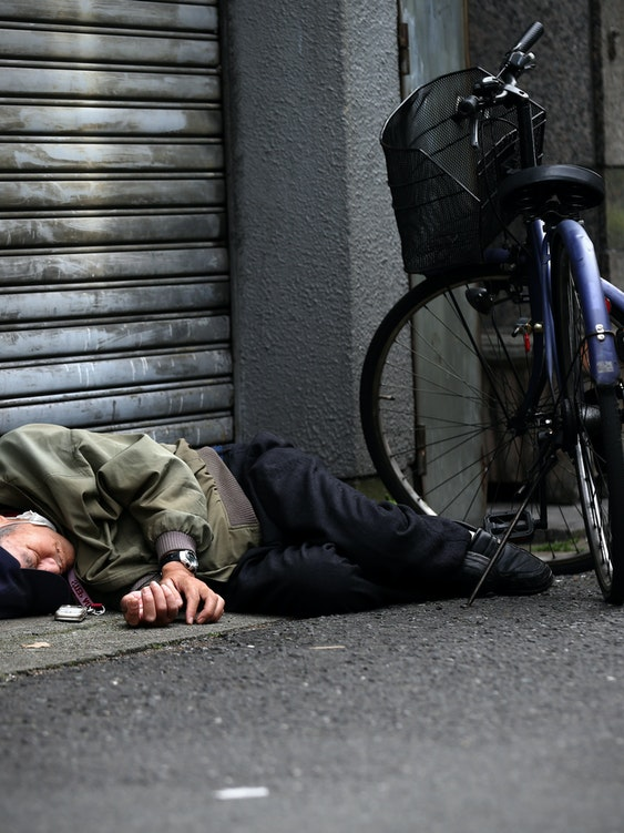 OSAKA, JAPAN - APRIL 24: A homeless man sleeps in the street near the slum area of Kamagasaki on April 24, 2016 in Osaka, Japan. Kamagasaki, a district in Japan's second largest city Osaka, is home to around 25,000 day labourers, jobless and homeless most of whom start each day hoping for an offer of manual labour and end it queuing for a ticket to access the shelter.  (Photo by Carl Court/Getty Images)