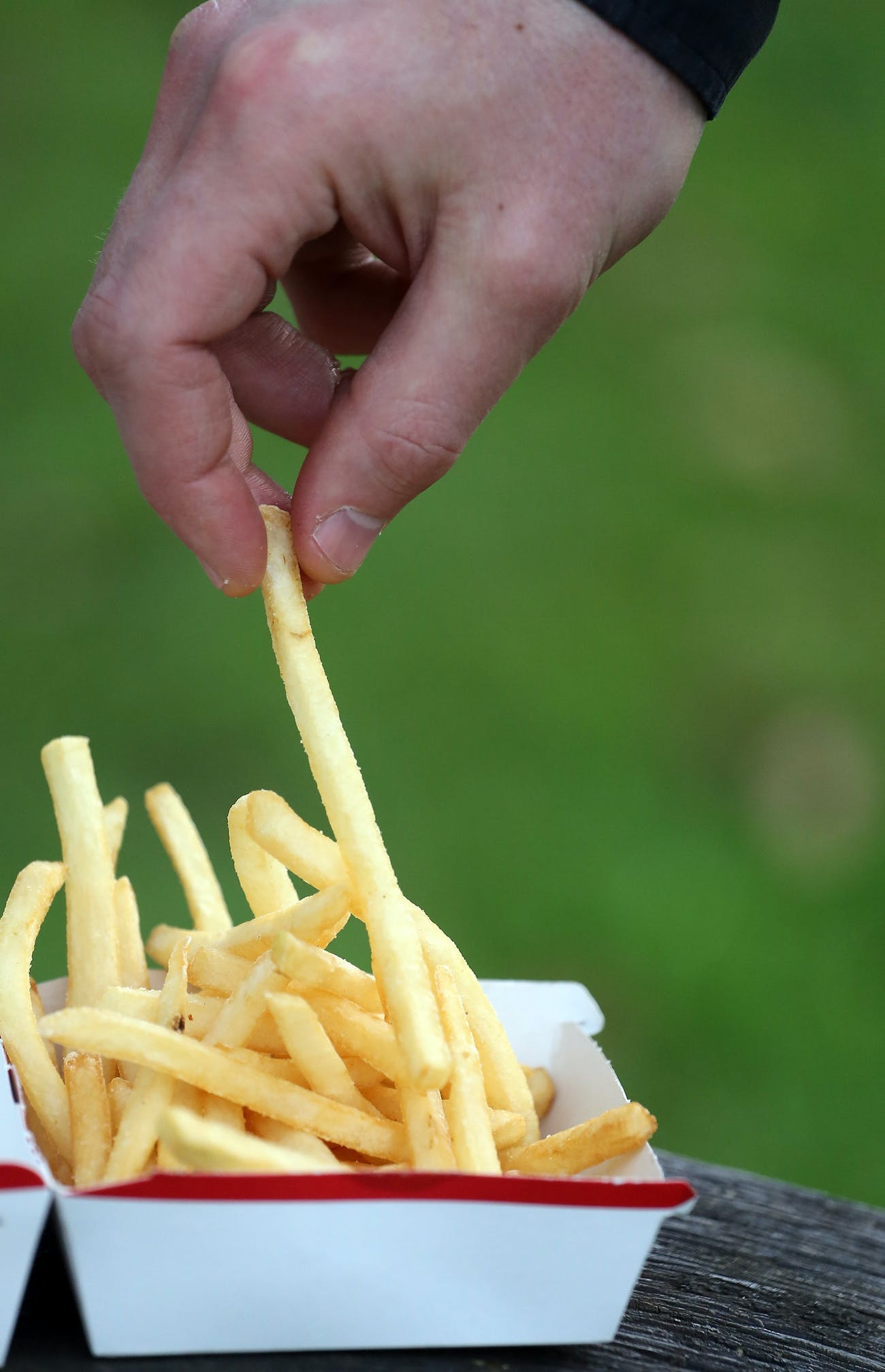BRISTOL, ENGLAND - JANUARY 07: In this photo-illustration a man eats French fries purchased from a fast food outlet on January 7, 2013 in Bristol, England. A government-backed TV advert - made by Aardman, the creators of Wallace and Gromit - to promote healthy eating in England, is to be shown for the first time later today. England has one of the highest rates of obesity in Europe - costing the NHS 5 billion GDP each year - with currently over 60 percent of adults and a third of 10 and 11 year olds thought to be overweight or obese. (Photo by Matt Cardy/Getty Images)