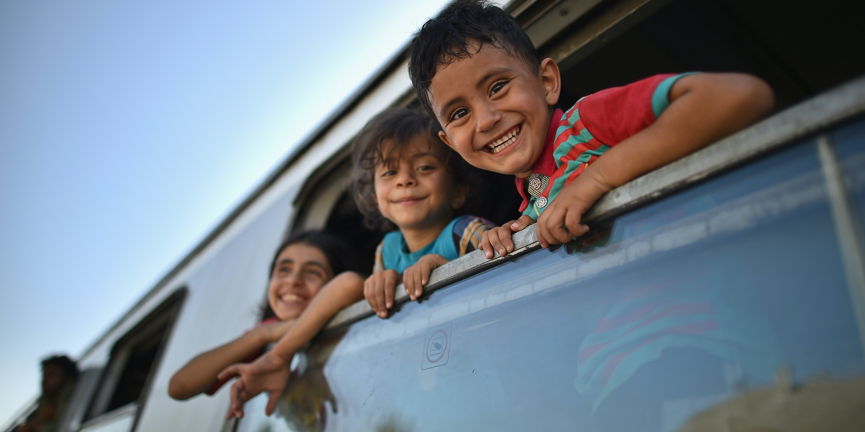 BELI MANASTIR, CROATIA - SEPTEMBER 18:  Young children smile a they look out of a train window as migrants board trains and busses at the train station in Beli Manastir, near Hungarian border on September 18, 2015 in Beli Manastir,Croatia. Officials are saying that they had no choice than to close eight road border crossings yesterday after more than 11,000 people entered the country since Hungary fenced off its border with Serbia earlier this week.  (Photo by Jeff J Mitchell/Getty Images)