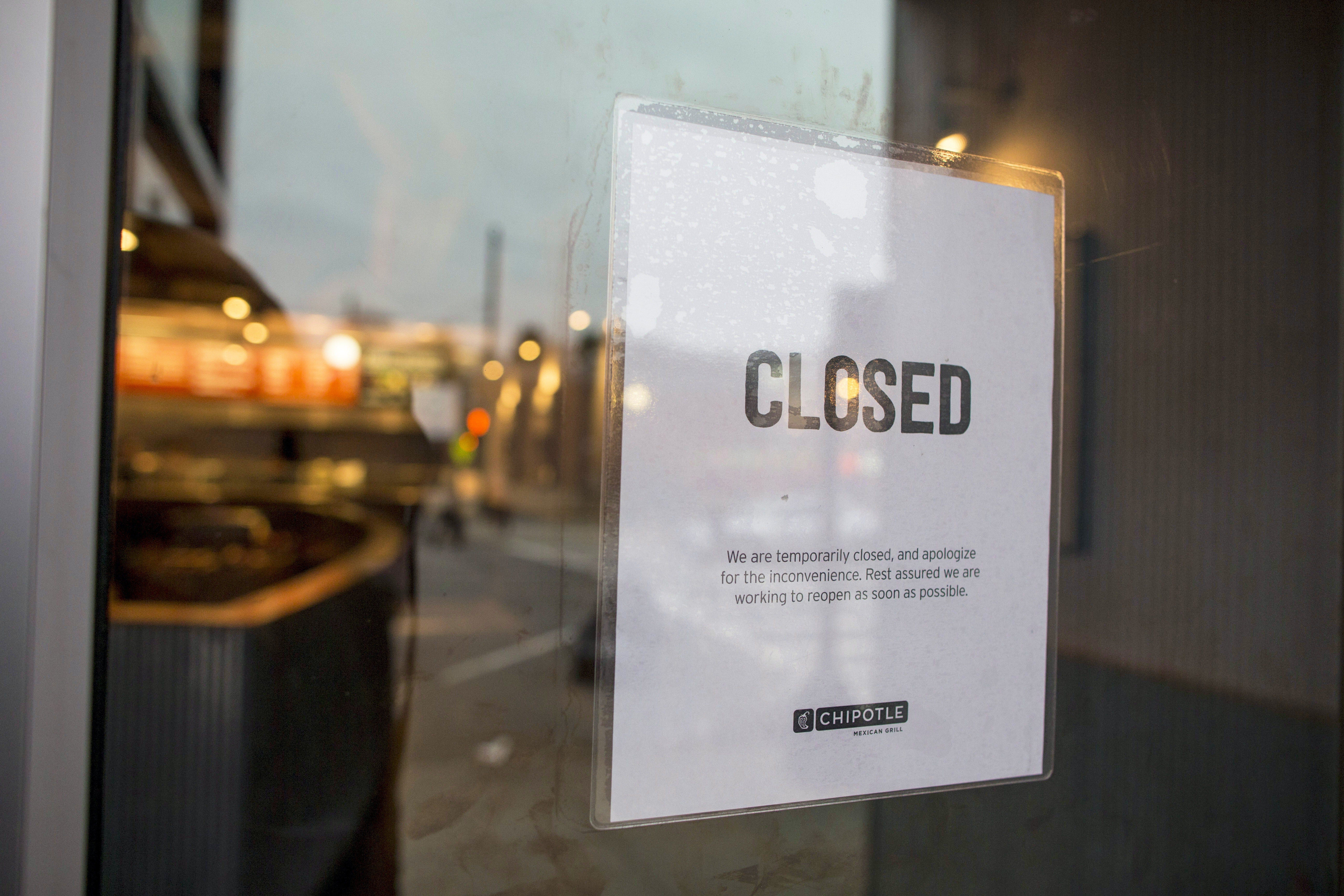 A sign showing that the Chipotle Mexican Grill seen at 1924 Beacon St. is closed on December 8, 2015 in Boston, Massachusetts. According to Boston College spokesman, 80 students have gotten sick after eating at the fast food chain.
