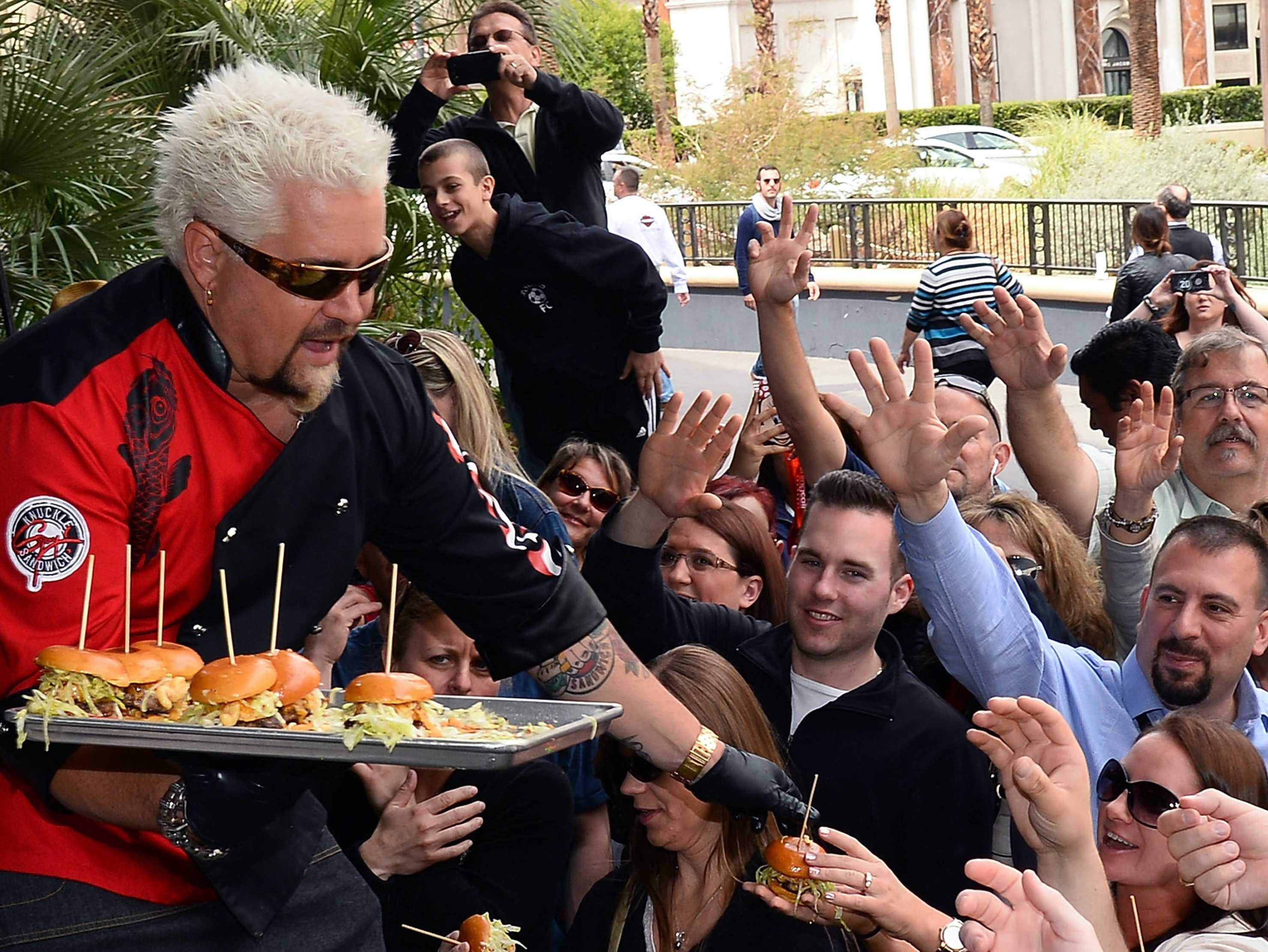 Chef and television personality Guy Fieri serves hamburgers to guests during a welcome event for Guy Fieri's Vegas Kitchen & Bar at The Quad Resort & Casino