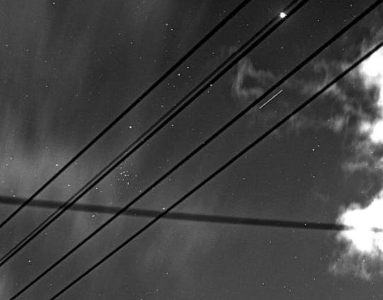 A two-second–long exposure through power and telephone lines shows a white line indicating the X-37B space plane in orbit.
