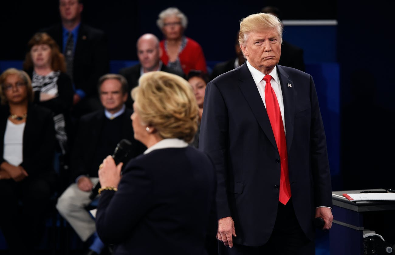 ST LOUIS, MO - OCTOBER 09: Democratic presidential nominee former Secretary of State Hillary Clinton (L) speaks as Republican presidential nominee Donald Trump listens during the town hall debate at Washington University on October 9, 2016 in St Louis, Missouri. This is the second of three presidential debates scheduled prior to the November 8th election. (Photo by Saul Loeb-Pool/Getty Images)