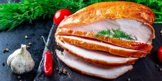 Delicious slicing of smoked chicken fillet with spices on a dark background