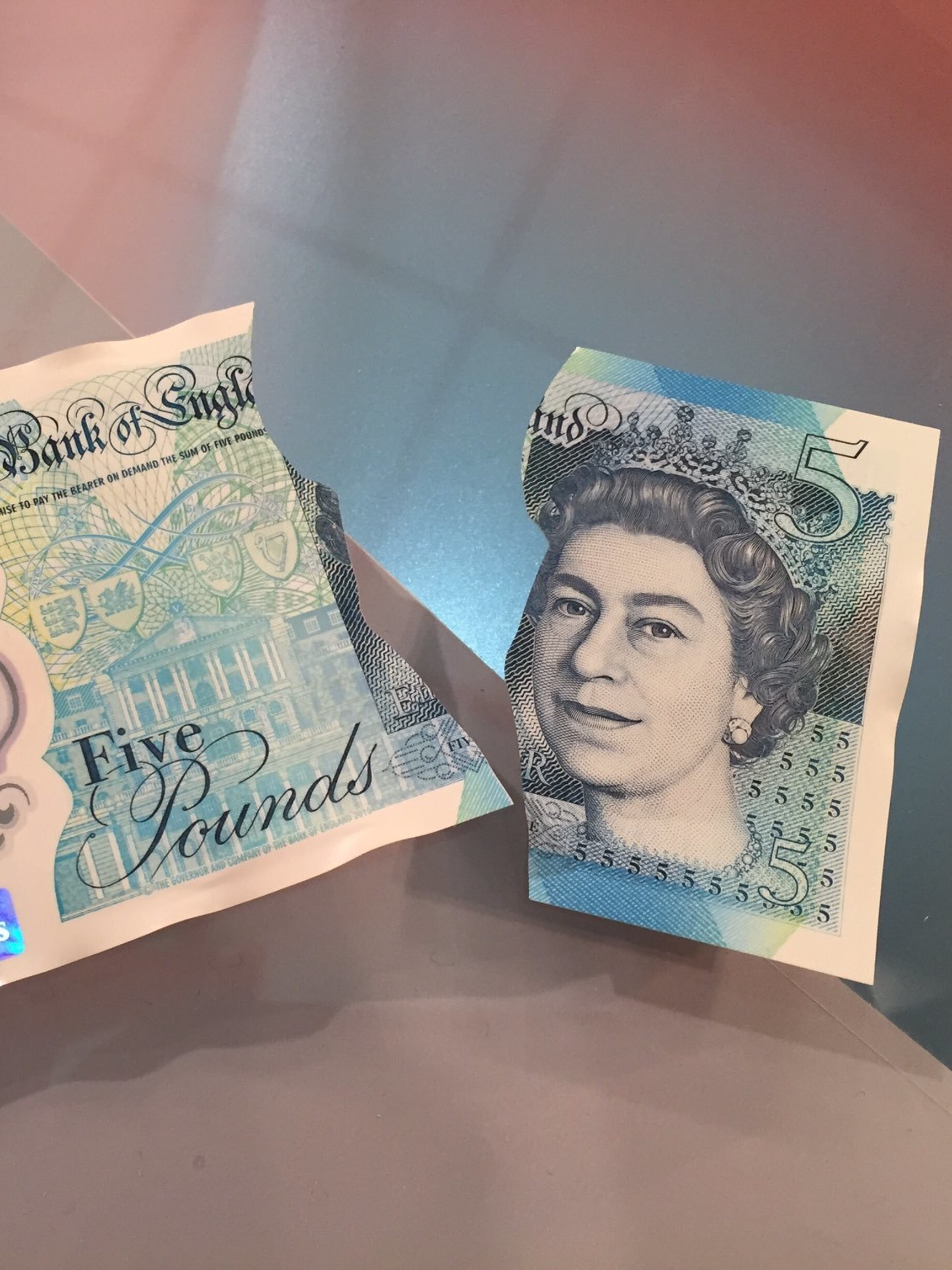 WOODSTOCK, ENGLAND - JUNE 02: The new polymer £5 note featuring Sir Winston Churchill is dipped in liquid as it is unveiled at Blenheim Palace on June 2, 2016 in Woodstock, England. The new fiver will be issued in September, and in a break from the current paper notes it will be printed on polymer, a thin flexible plastic film, which is seen as more durable and more secure. (Photo by Joe Giddens - WPA Pool/Getty Images)