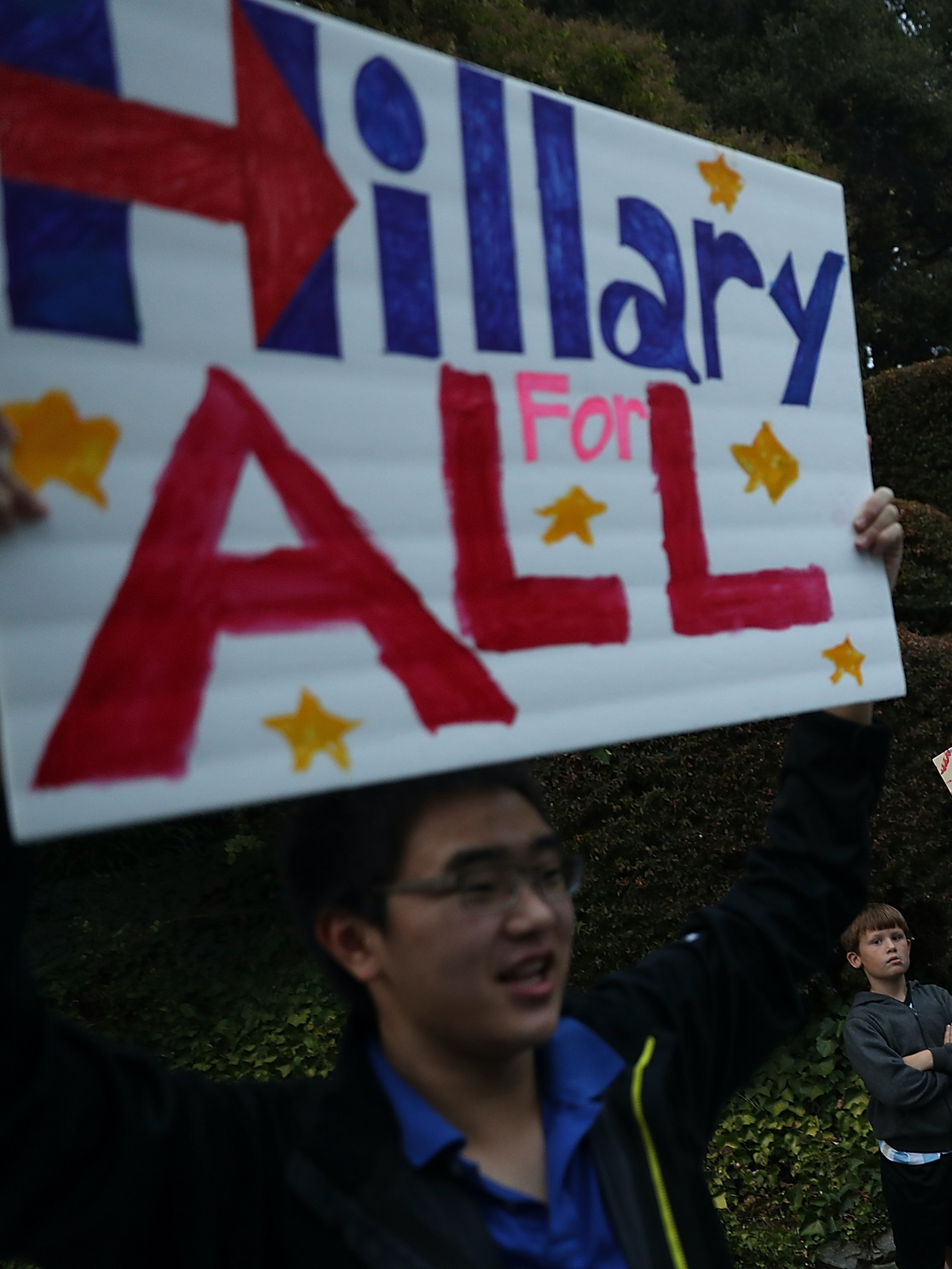 Young supporters hold signs outside of a fundraiser for democratic presidential nominee former Secretary of State Hillary Clinton.