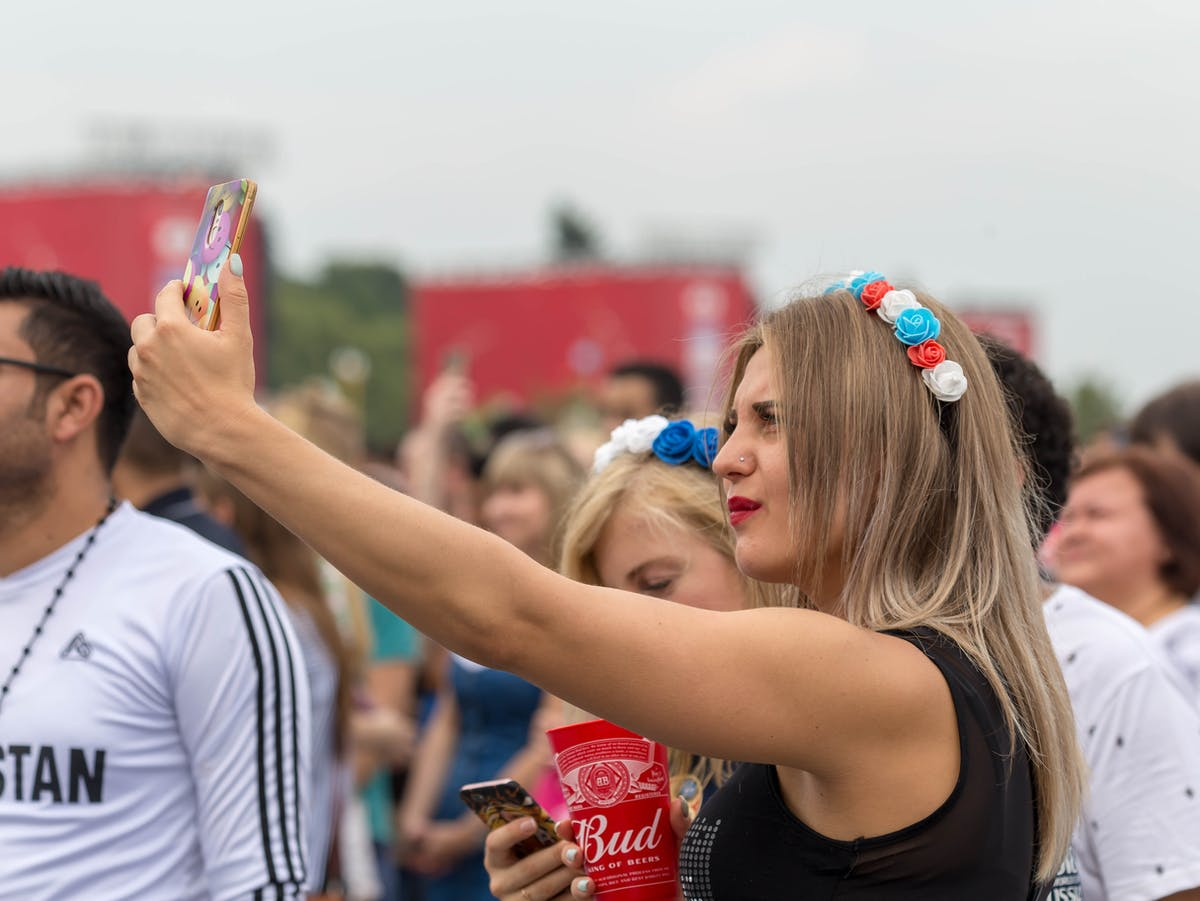 Girl with fake flowers in her hair taking a selfie