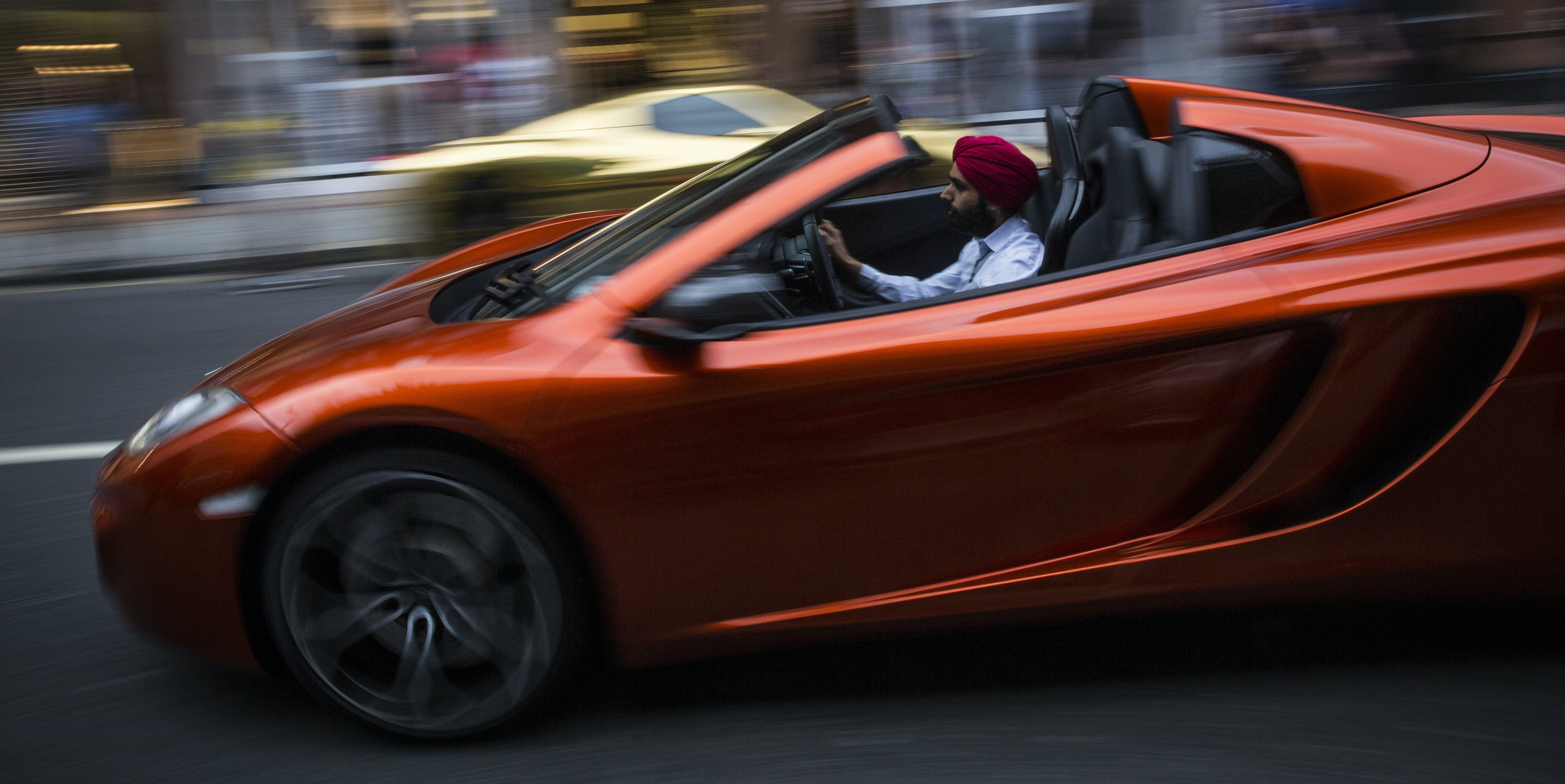 LONDON, ENGLAND - AUGUST 08:  A man drives down Sloane Street in a Mclaren supercar on August 8, 2014 in London, England. Tourists and car enthusiasts have been flocking to the wealthy London district to see some of the world's most expensive and extravagant super cars. Many of the rich owners from Saudi Arabia and Kuwait come to London to escape the summer heat at home and to show off their cars before moving on to other European cities such as Paris and Cannes.  (Photo by Dan Kitwood/Getty Images)