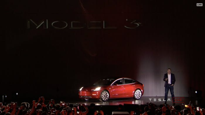 Elon Musk shows off the Tesla Model 3.