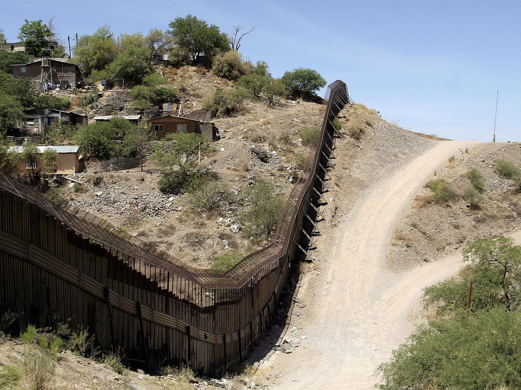 NOGALES, AZ -  MAY 14:  A steel wall separates Nogales, Sonora, Mexico (L) from a U.S. Border Patrol agent in his sector May 14, 2006 in Nogales, Arizona. U.S. President George W. Bush will address the nation on the immigration issue May 15.  (Photo by Jeff Topping/Getty Images)