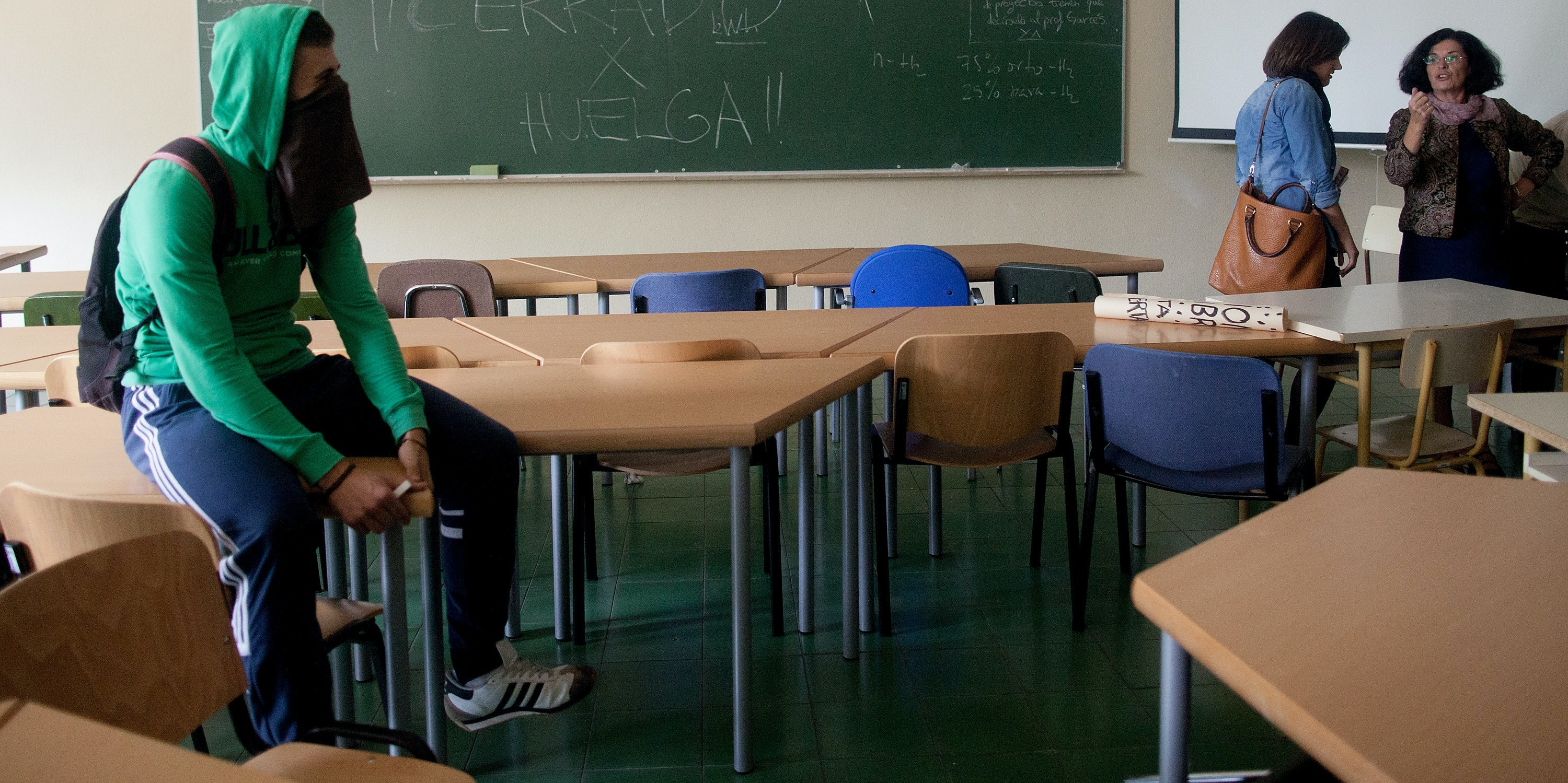 MADRID, SPAIN - OCTOBER 24:  A student on strike (L) sits on desk in a classroom while a teacher speaks (R) and the blackboard reads 'closed by strike' at the School of Aeronautic Engineers in Ciudad Universitaria on October 24, 2013 in Madrid, Spain. The Spanish Parliament recently approved a controversial reform of the educational system, which passed by the ruling right wing People's Party (PP) using their absolute majority and not backed by any other political party. The students are on a three day strike to protest against the new law, which will need to be approved by the senate next month and are calling for the resignation of Education Minister, Jose Ignacio Wert.  (Photo by Pablo Blazquez Dominguez/Getty Images)