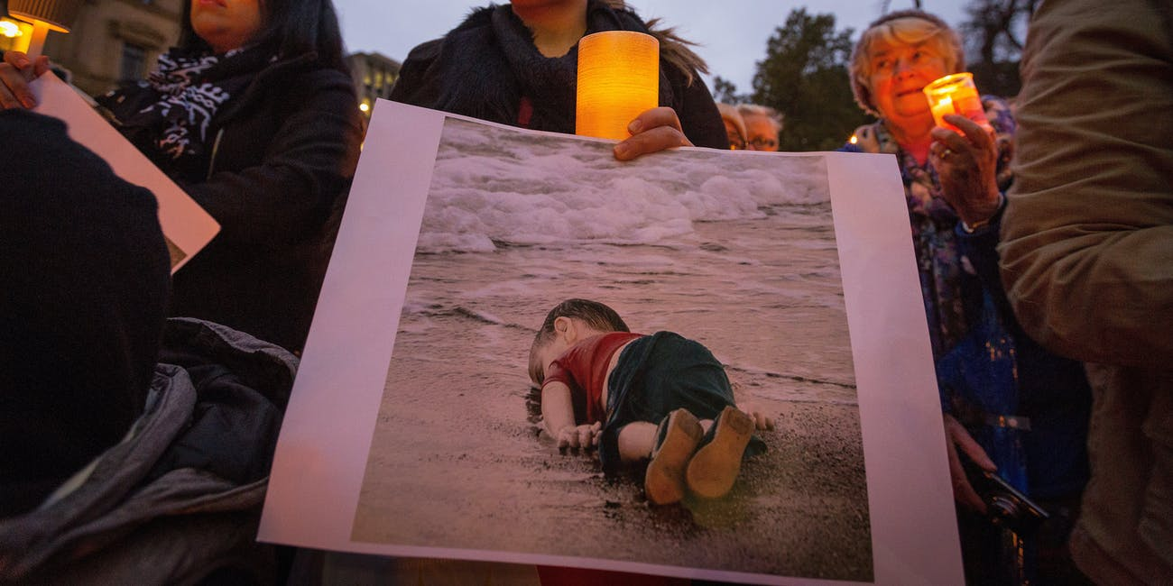woman hold's photo of Aylan Kurdi at a vigil