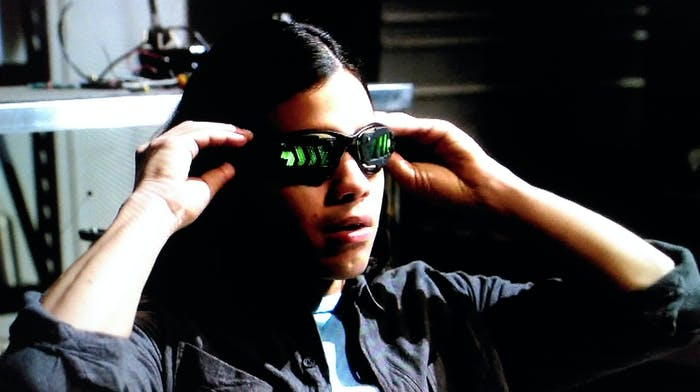 """Cisco tries on his new vibe-inducing goggles, on the CW show """"The Flash."""""""