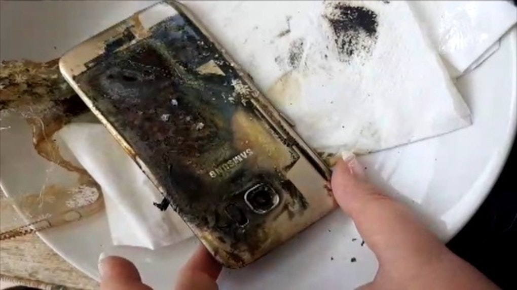 A woman holds a burnt Samsung Galaxy S7 on a dinner plate after it spontaneously combusted.