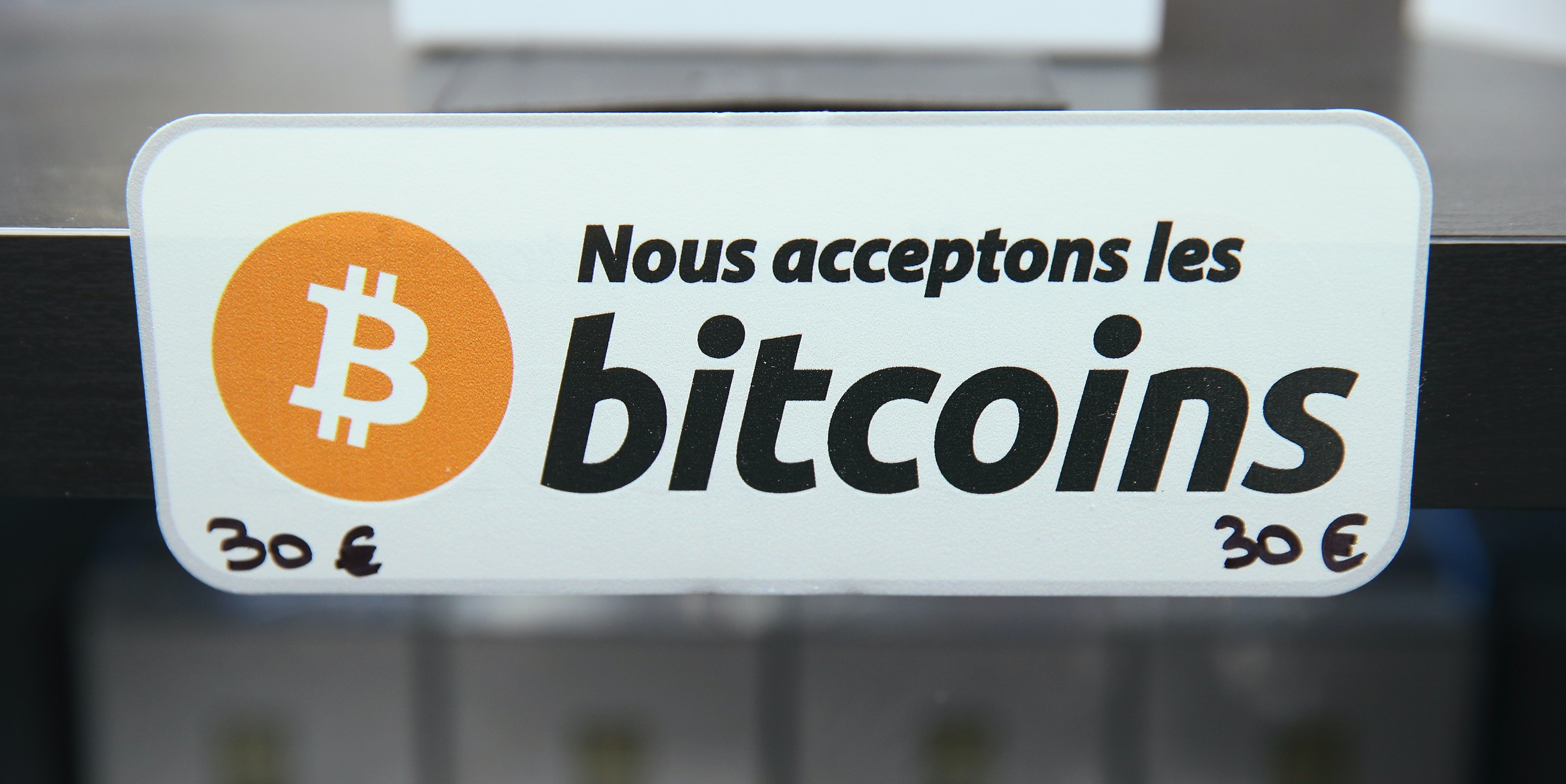 A sign in French that reads: 'We accept bitcoins' hangs at a display of the LedgerWallet Nano USB stick that enables security-protected transactions with bitcoins at the 2015 CeBIT technology trade fair on March 16, 2015 in Hanover, Germany. China is this year's CeBIT partner. CeBIT is the world's largest tech fair and will be open from March 16 through March 20.
