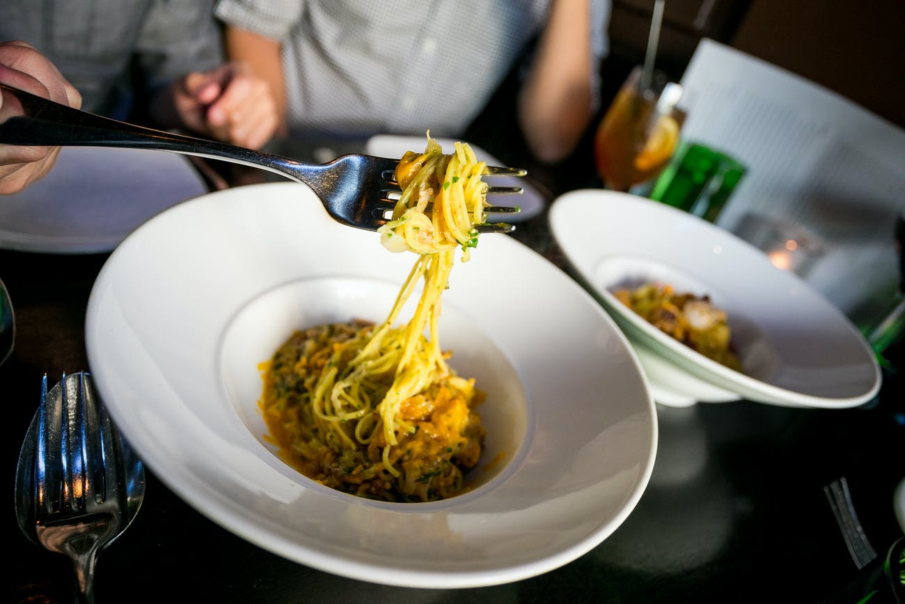 fork lifting pasta out of a bowl