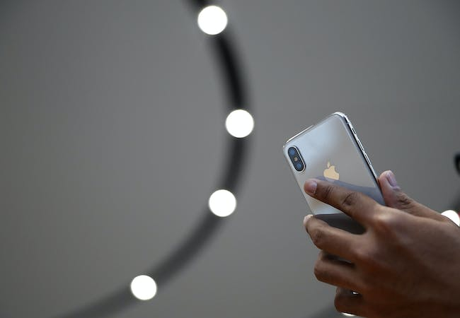 An attendee looks at a new iPhone X during an Apple special event at the Steve Jobs Theatre on the Apple Park campus on September 12, 2017, in Cupertino, California.