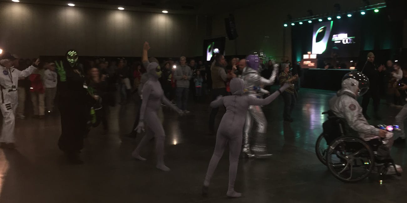 AlienCon cosplayers make they way to the stage for a costume contest.