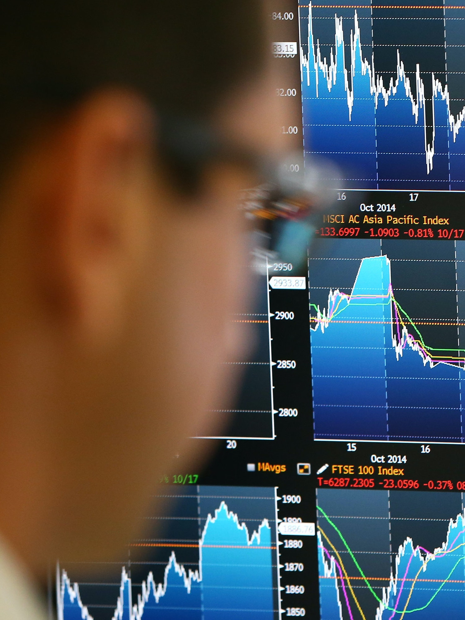 LONDON, ENGLAND - OCTOBER 20:  An employee views trading screens at the offices of Panmure Gordon and Co on October 20, 2014 in London, England. Markets stabilised over the weekend following global turbulence amid fears over the Ebola virus and global economic concerns.  (Photo by Carl Court/Getty Images)