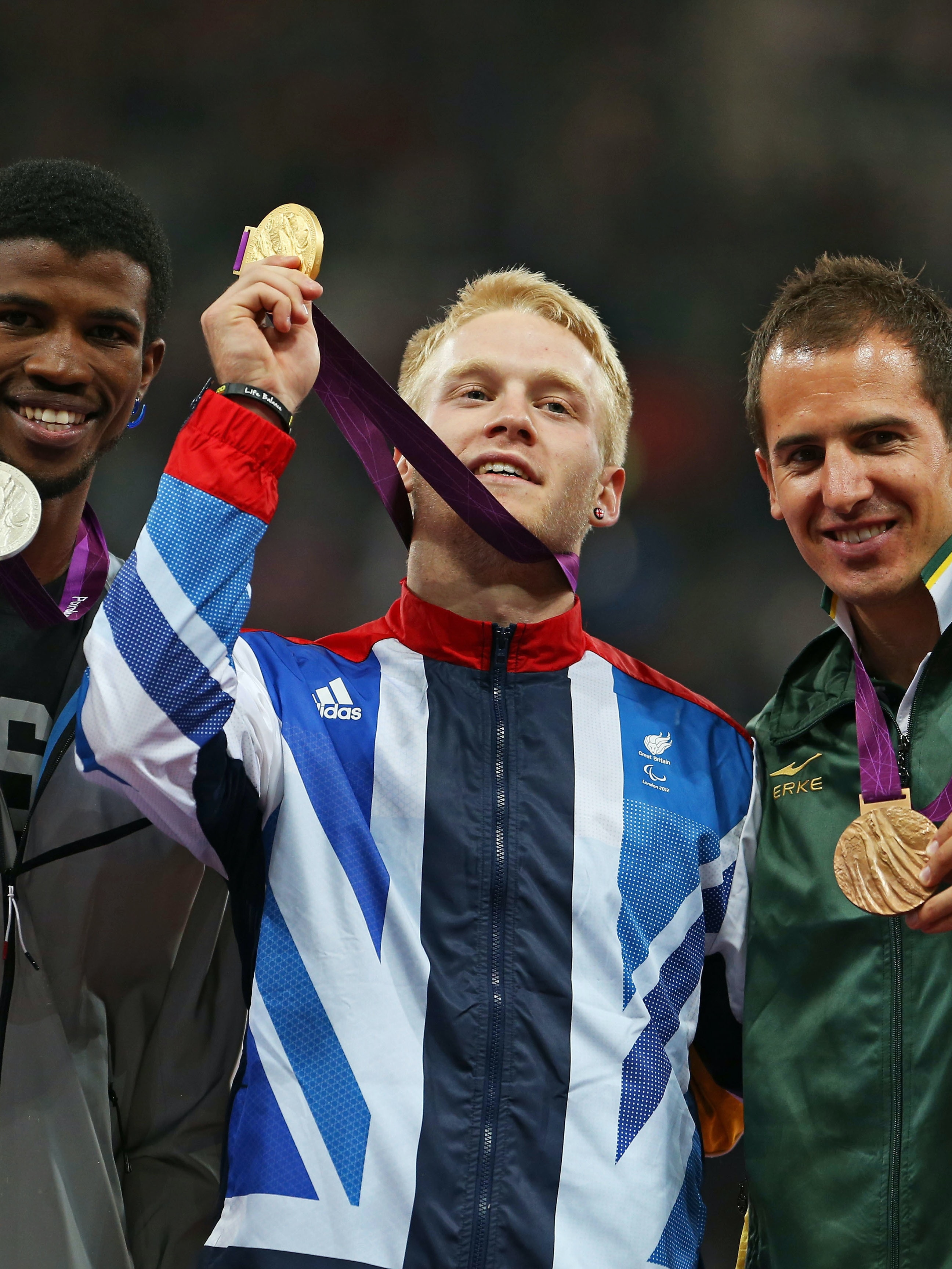 LONDON, ENGLAND - SEPTEMBER 06:  (L-R) Silver medalist Richard Browne of the United States , Gold medalist Jonnie Peacock of Great Britain, Bronze medalist Arnu Fourie of South Africa pose on the podium during the victory ceremony for the Men's 100m - T44 Final on day 8 of the London 2012 Paralympic Games at Olympic Stadium on September 6, 2012 in London, England.  (Photo by Julian Finney/Getty Images)