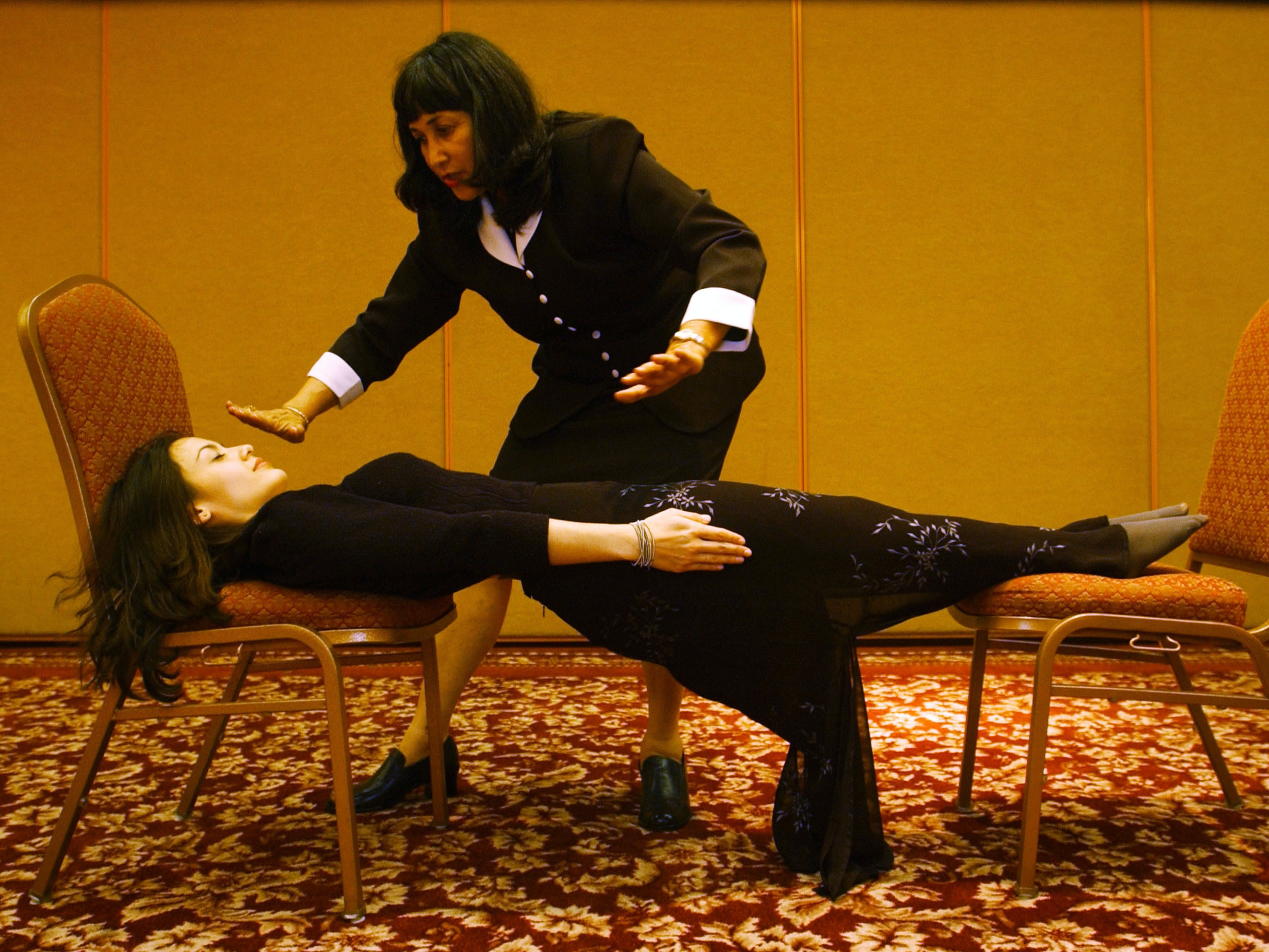 392233 03: Hypnotherapist and actress Cathy Kay is stretched between chairs after becoming rigid as a board under the hypnotic suggestion of Shelley Stockwell, president and founder of the International Hypnosis Federation & Creativity Institute, at the International Hypnosis Federation''s Mind, Body, Spirit, Fun Conference, July 20, 2001 in Long Beach, CA. (Photo by David McNew/Getty Images)