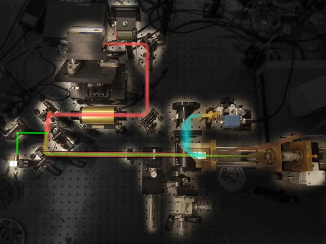 Picture of the experimental setup showing the different components of the system and highlighting the path followed by the QCL light (red) and THz radiation (blue).