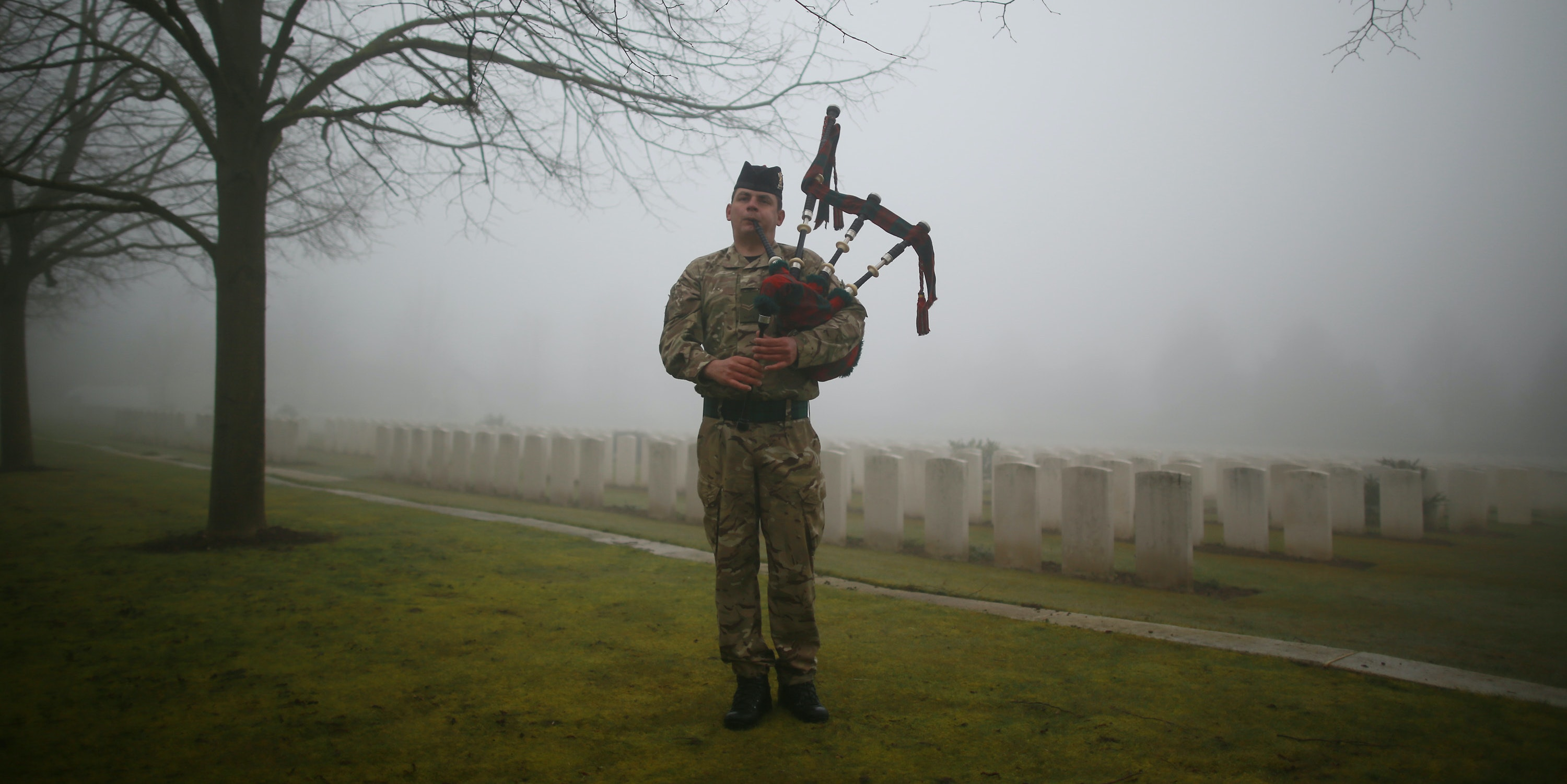 LOOS-EN-GOHELLE, FRANCE - MARCH 13:  Corporal Stuart Gillies of The 2nd Battalion The Royal Regiment of Scotland practices his bagpipes in Loos British Cemetery during a rehearsal for a re-burial ceremony on March 13, 2014 in Loos-en-Gohelle, France. Almost 100 years after they were killed in action in the World War One battle of Loos in 1915, twenty British soldiers will be re-interred in the Commonwealth War Graves Commission Loos British Cemetery in Northern France. Private William McAleer, from the 7th Battalion the Royal Scottish Fusiliers, was found with his identity disc, but others found with him remain unidentified and will be buried as soldiers Known unto God.  (Photo by Peter Macdiarmid/Getty Images)