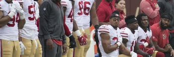 San Francisco 49ers players take the knee during the national anthem.