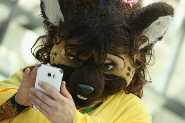 BERLIN, GERMANY - AUGUST 17: A participant, or furry, as the participants prefer to be called, attempts to use a smartphone upon his arrival at the Estrel Hotel for the 2016 Eurofurence furries gathering on August 17, 2016 in Berlin, Germany. Approximately 2,500 furries from all over the world will participate in the four-day convention that includes dance parties, fashion shows and art events. Furries describe themlelvs as anthroporphic actors and the movemment has its roots in science fiction and fantasy genres going back to the 1980s. (Photo by Sean Gallup/Getty Images)