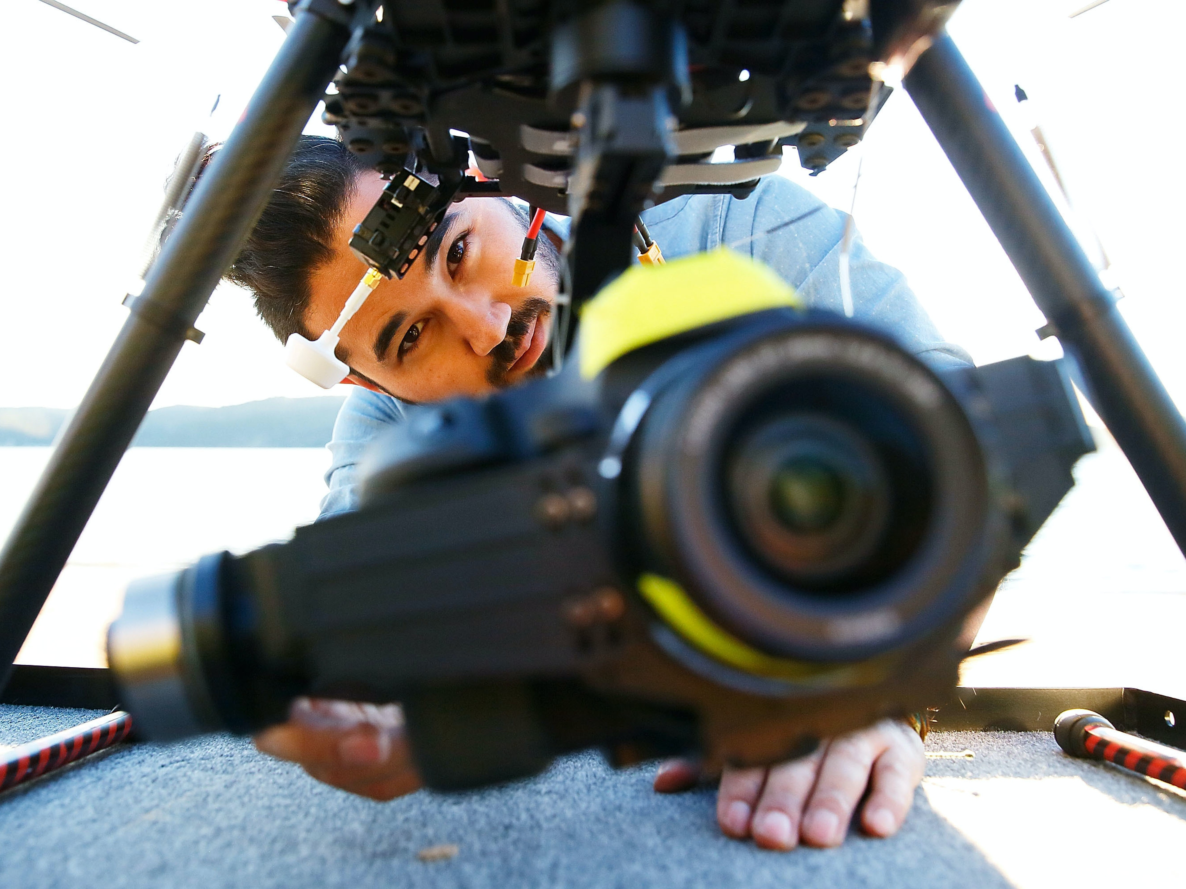 SYDNEY, AUSTRALIA - JULY 04: Drone operator, Ken Butti checks the camera gimbal of the custom built DJI s1000 Drone prior to flight at Palm Beach on July 4, 2014 in Sydney, Australia. Commercial and recreational UAV (Unmanned Aerial Vehicles) sales in Australia have regulators concerned about safety, privacy and security, while the commercial industries of mining, farming, property, and sport are embracing the new technology. Under the current CASA (Civil Aviation Safety Authority) regulations all unmanned aircraft weighing more than 2kg need to have a UAS operators certificate. Licensed operators are not allowed to fly above 400ft, not within 5km of an airfield boundary and can't fly within 30 metres of people not involved with the operation.  (Photo by Brendon Thorne/Getty Images)