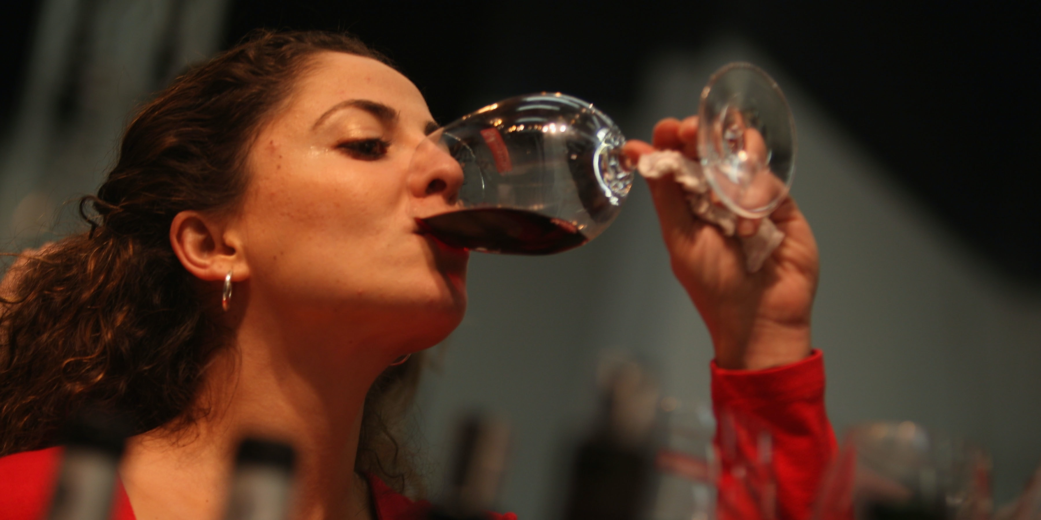 TEL AVIV, ISRAEL - FEBRUARY 26: An Israeli woman tastes a red wine at the three-day 2nd International Wines Exhibition which opened February 26, 2008 in Tel Aviv. The fair is a showcase for wines and wineries from Israel and around the world, with special emphasis on the exhibition of the Israeli rising wine industry.  (Photo by David Silverman/Getty Images)