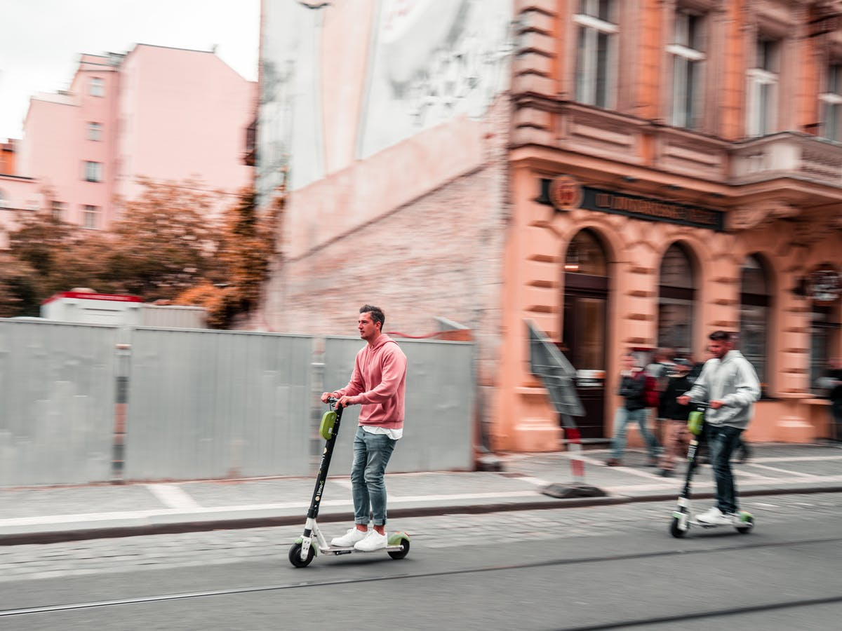 men riding scooters without helmets