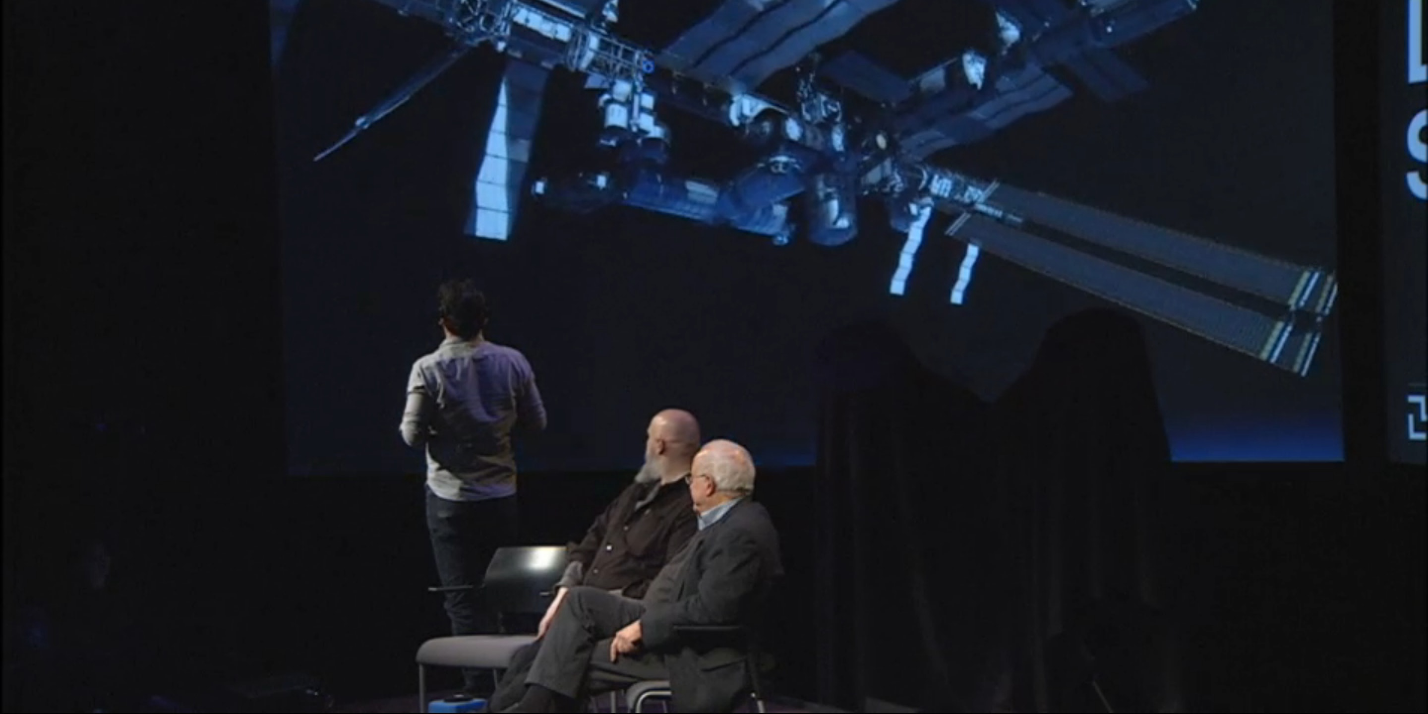 Writer Warren Ellis and visual effects designer Douglas Trumbull look on as visual effects supervisor Ben Grossman approaches the International Space Station in virtual reality.