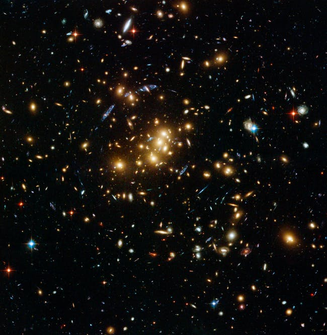 An international team of astronomers using the NASA/ESA Hubble Space Telescope has discovered a ghostly ring of dark matter that was formed long ago during a titanic collision between two massive galaxy clusters. It is the first time that a dark matter distribution has been found that differs substantially from the distribution of ordinary matter. This image shows the galaxy cluster Cl 0024+17 (ZwCl 0024+1652) as seen by Hubble's Advanced Camera for Surveys. The image displays faint faraway background galaxies that had their light bent by the cluster's strong gravitational field. By mapping the distorted light and using it to deduce how dark matter is distributed in the cluster, astronomers spotted the ring of dark matter. One of the background galaxies is located about two times further away than the yellow cluster galaxies in the foreground, and has been multiple-imaged into five separate arc-shaped components, seen in blue.