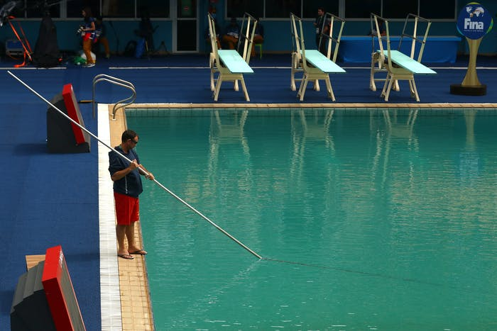 A lifeguard cleans the still green diving pool before the Women's Diving 3m Springboard Preliminary Round on August 12, 2016 in Rio.