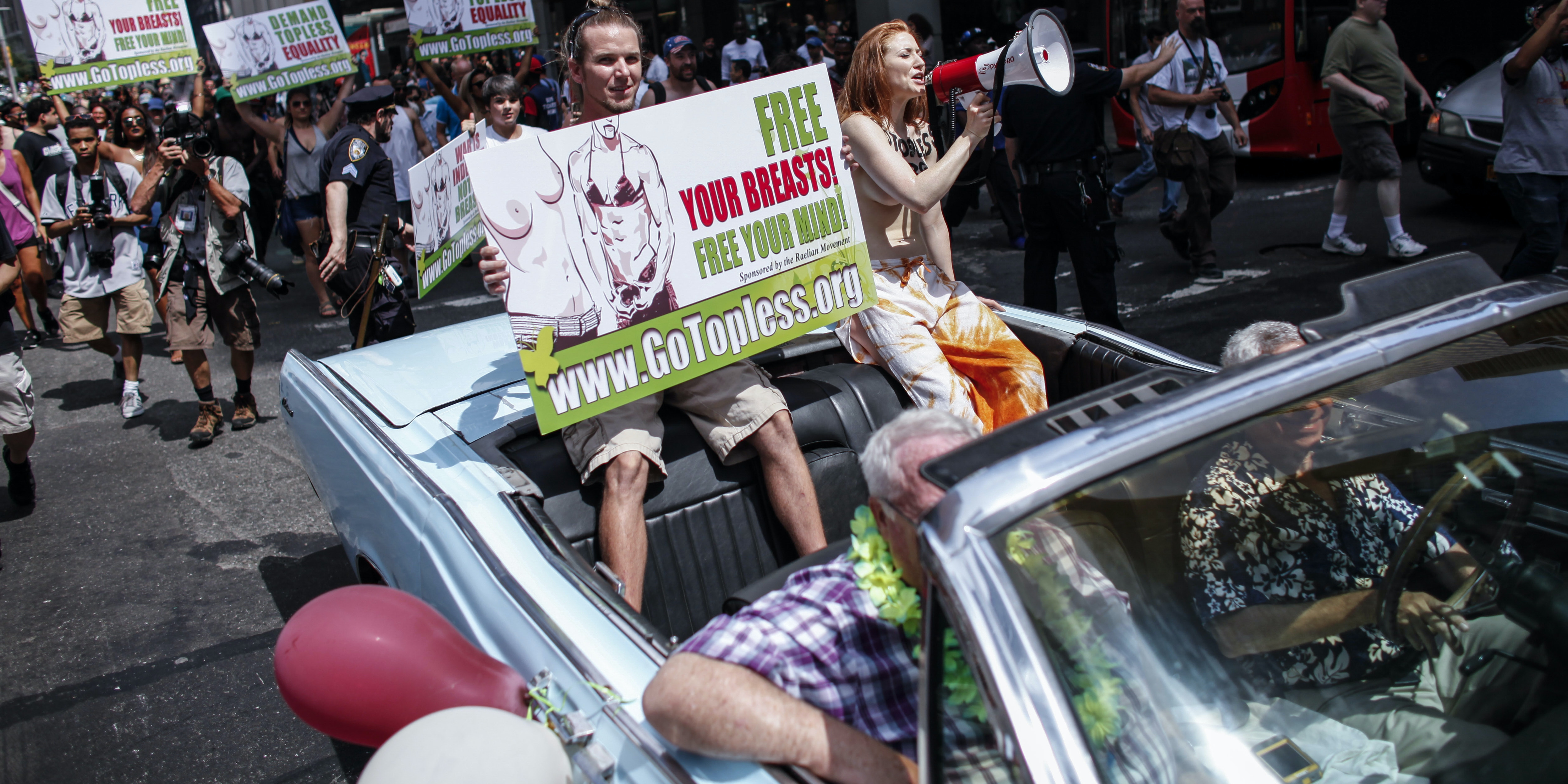 People participate in the GoTopless pride parade in Manhattan on August 23, 2015.
