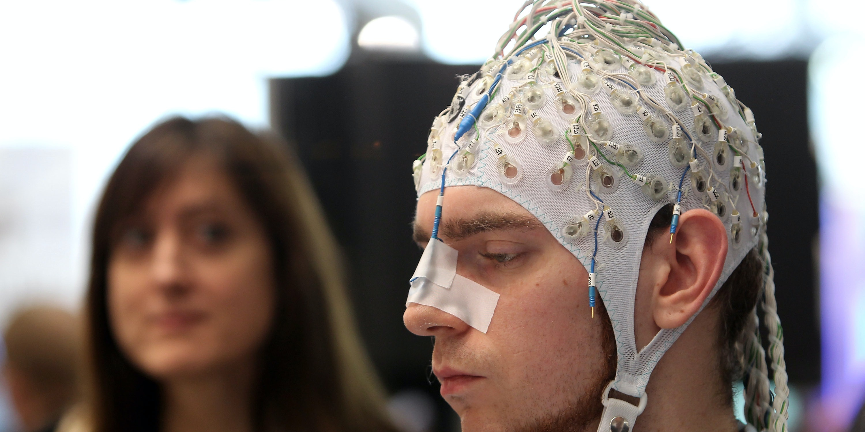 HANNOVER, GERMANY - MARCH 02:  A young woman watches a man, wearing an EEG brain scanning apparatus on his head, play a pinball game solely through willing the paddles to react with his brain at the Berlin Brain Computer Interface research consortium stand at the CeBIT Technology Fair on March 2, 2010 in Hannover, Germany. CeBIT will be open to the public from March 2 through March 6.  (Photo by Sean Gallup/Getty Images)