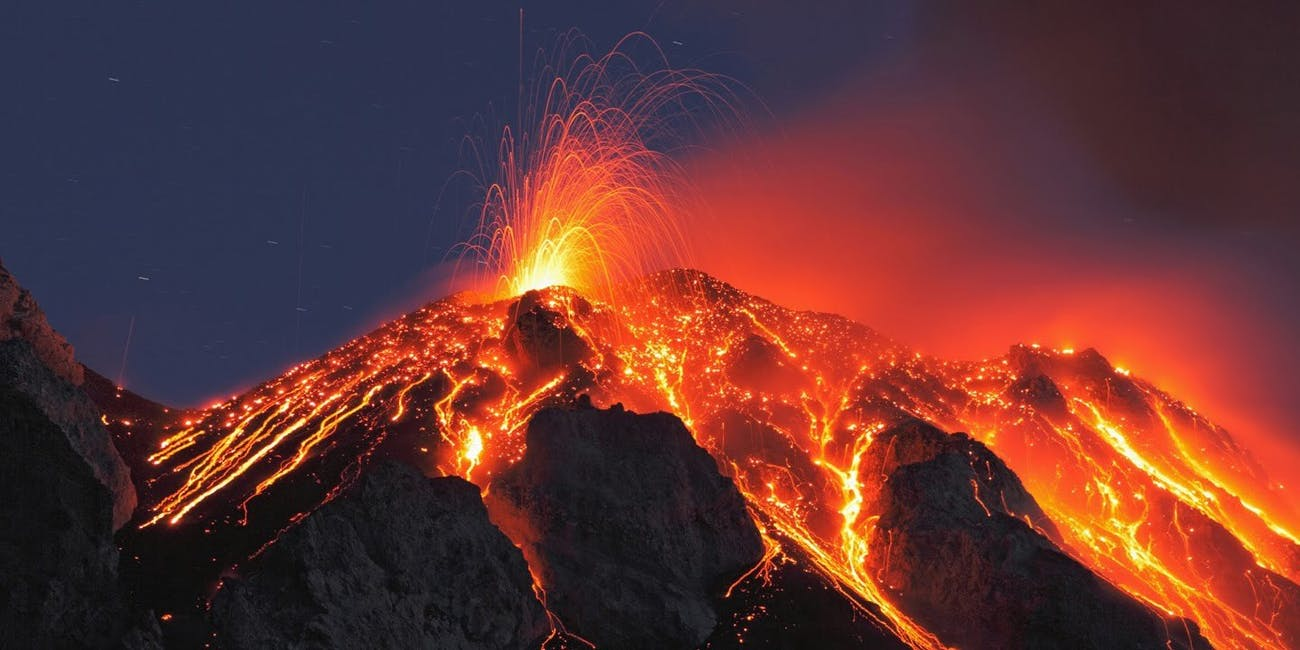 A meteor dashes behind an erupting volcano.