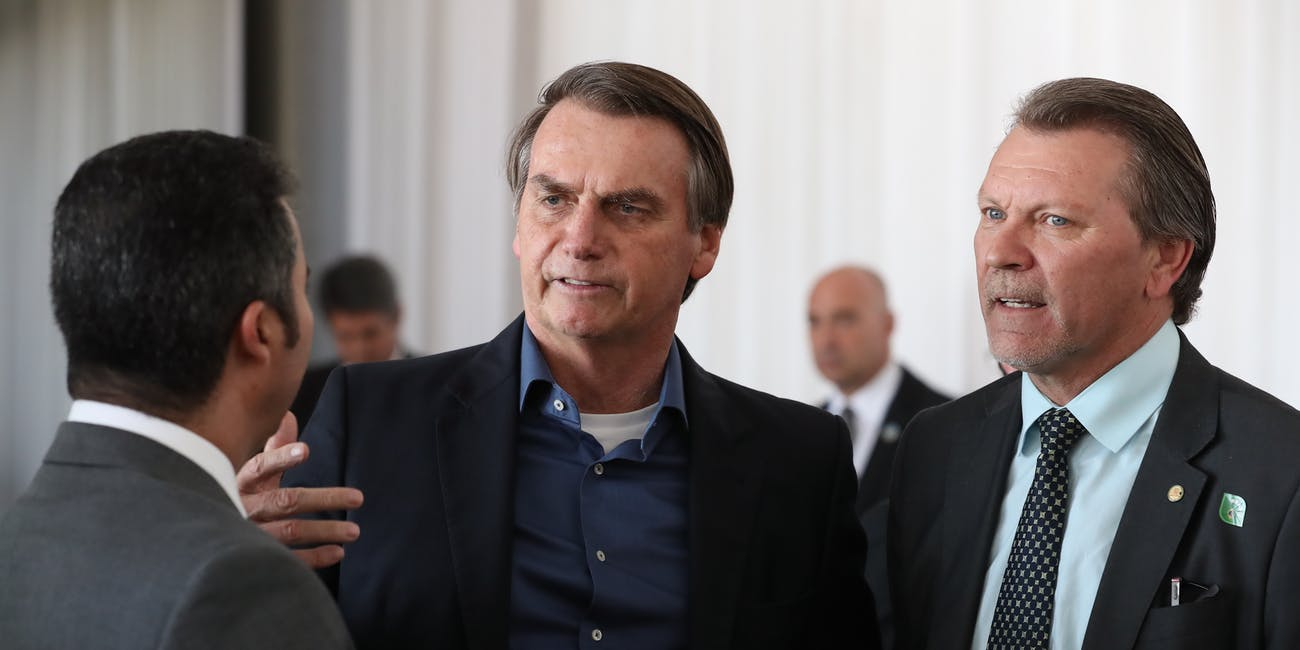 Brazilian President Jair Bolsonaro talks to two other men
