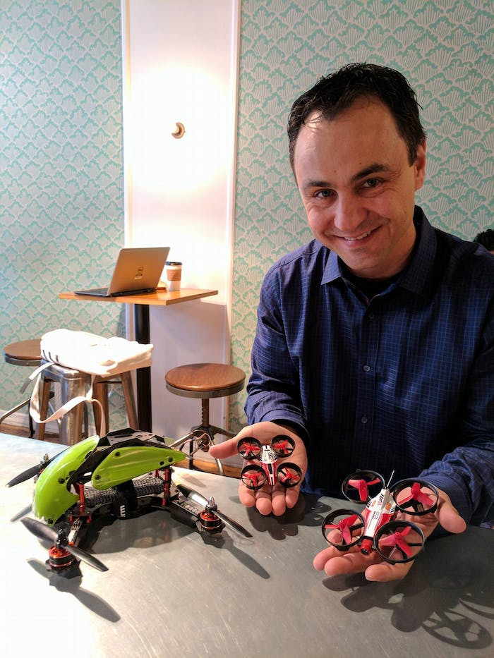 Brad Foxhoven, founder and CEO of DR1 racing, holds the entry-level drone on the left and the micro racing drone on the right.  The drone on the table is a regular racing drone, which is used in the DR1 Champions Series.